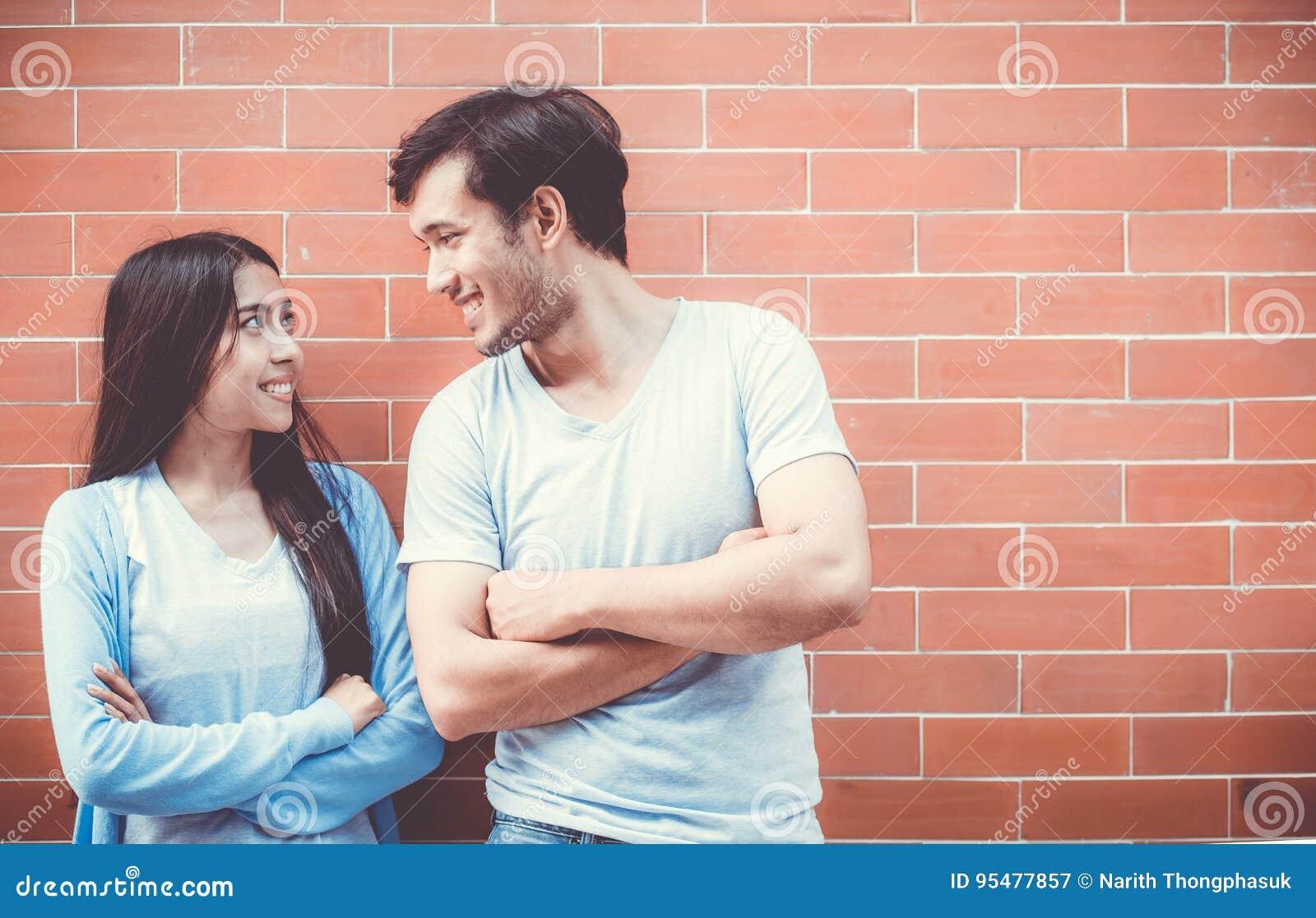 Potomstwa dobierają się azjatykcią atrakcyjną przyglądającą twarz i ono uśmiecha się