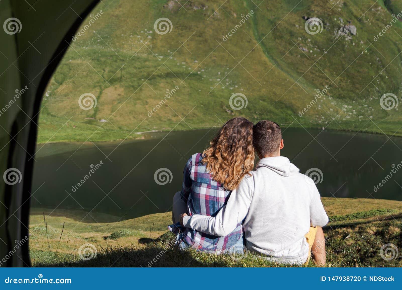 Potomstwa dobierają się uściśnięcia each inny przed namiotem w górach Switzerland