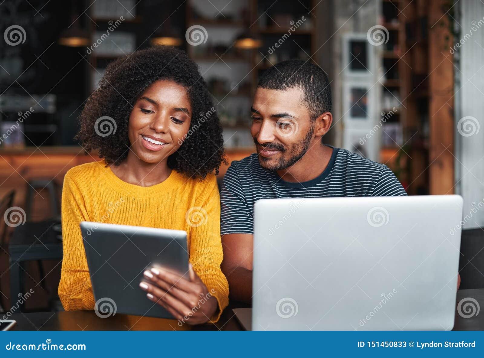Potomstwa dobierają się z laptopem i cyfrową pastylką w café