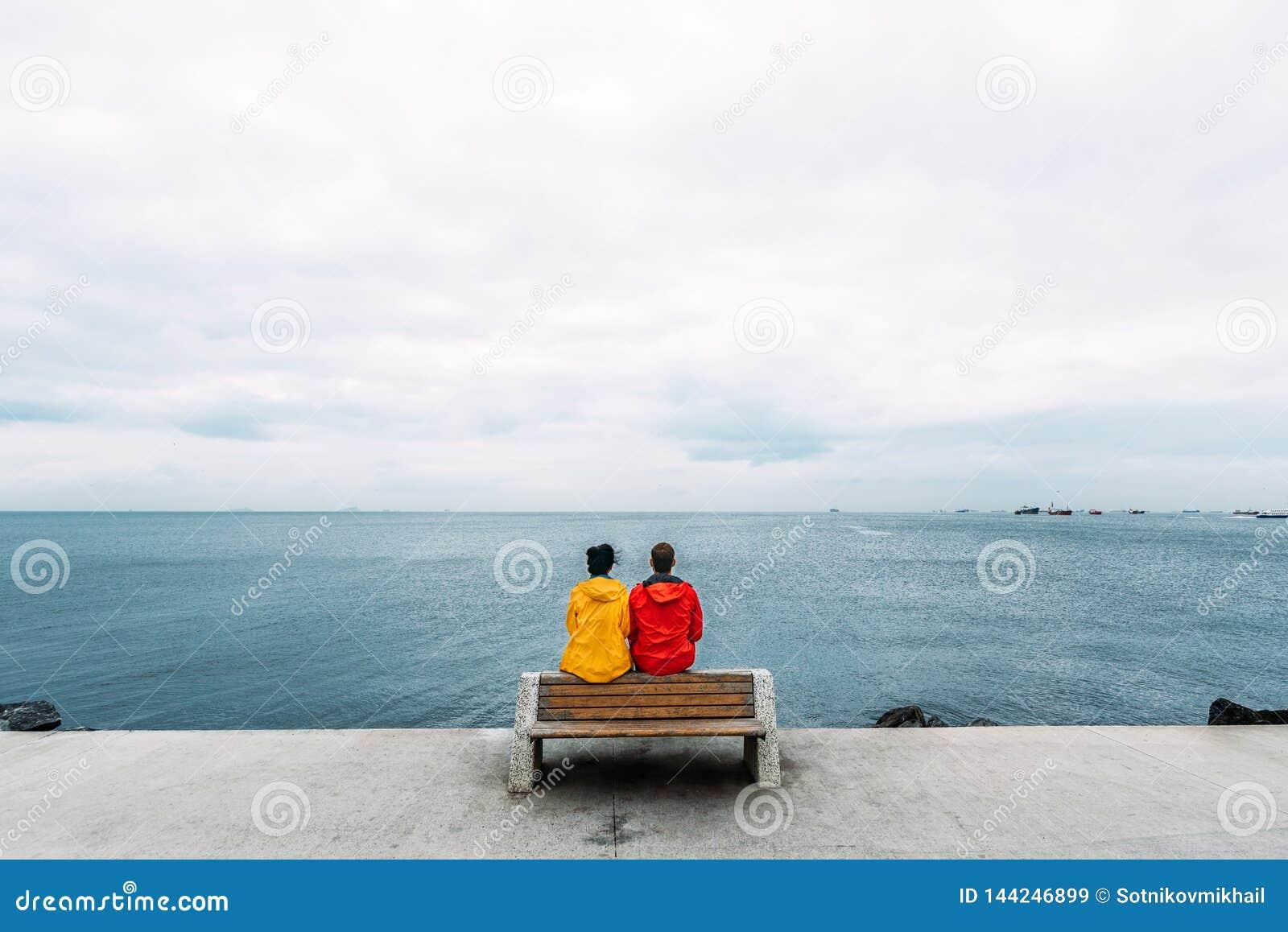 Potomstwa dobieraj? si? obsiadanie na ?awce morzem target1_0_ m??czyzna kobieta Ludzie siedz? na ?awce i patrzej? morze Tury?ci