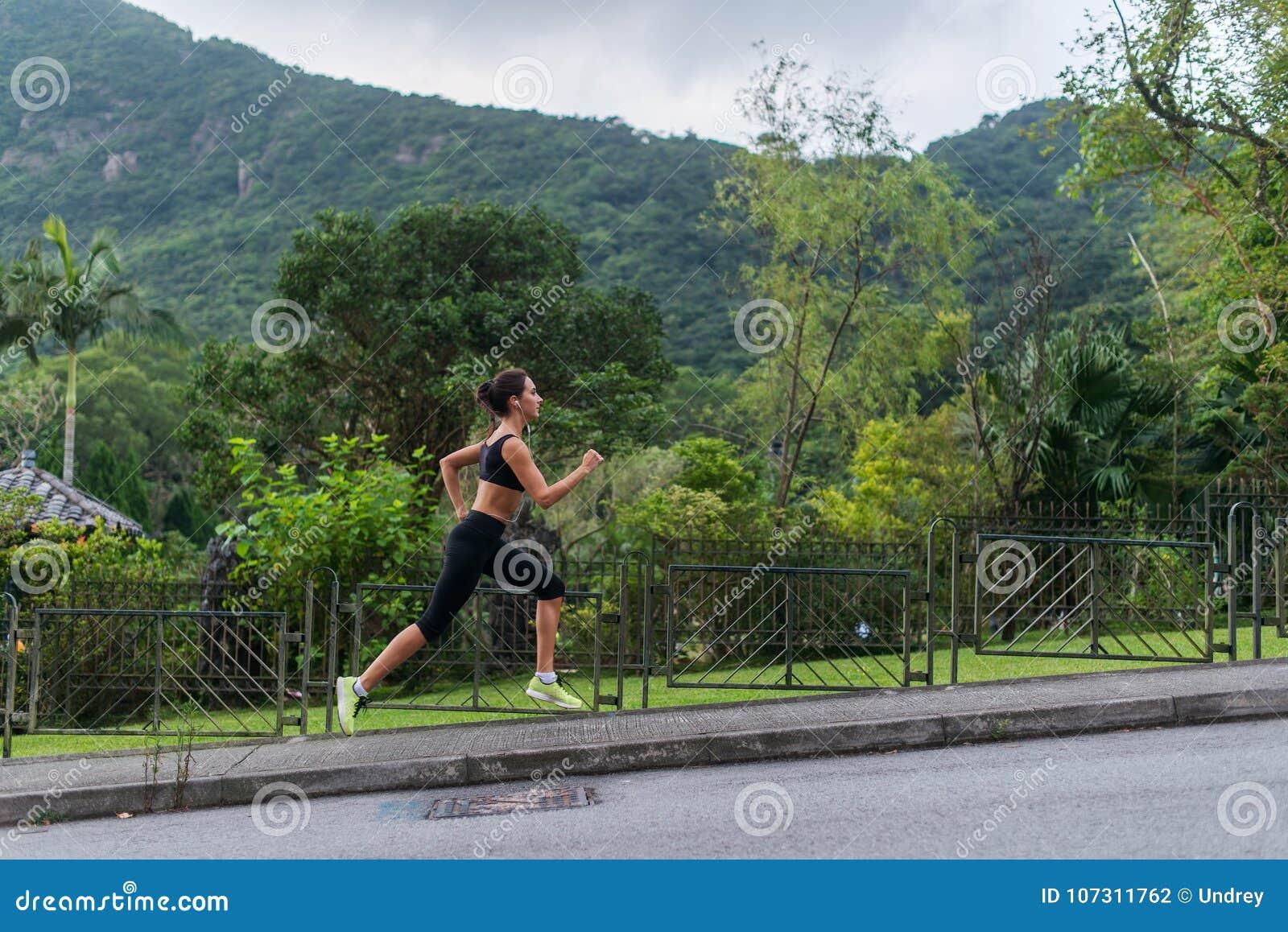 Potomstwa dostosowywali kobiety robi cardio ćwiczeniu z zielonym góra krajobrazem w, słuchający muzyka, biega outdoors