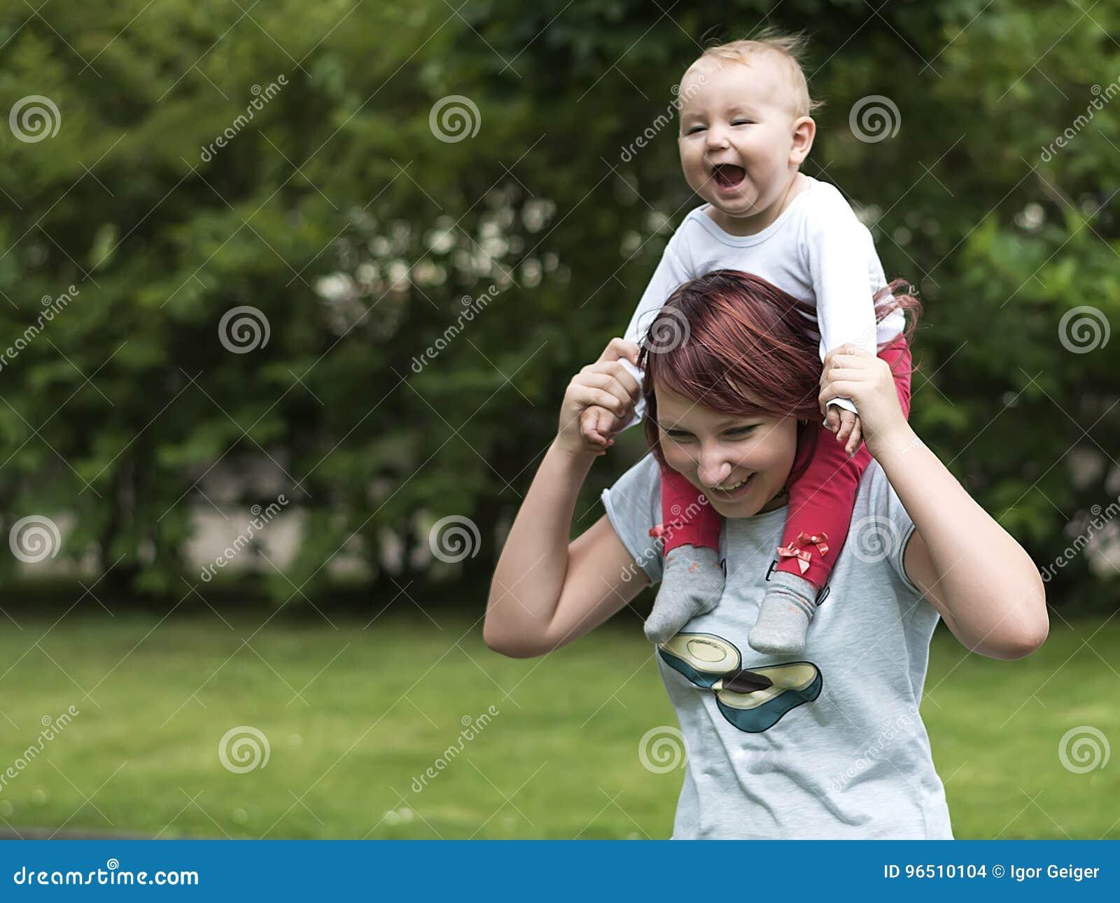 Potomstwa matkują szczęśliwie wydawać czas z młodym dzieckiem w lato parku