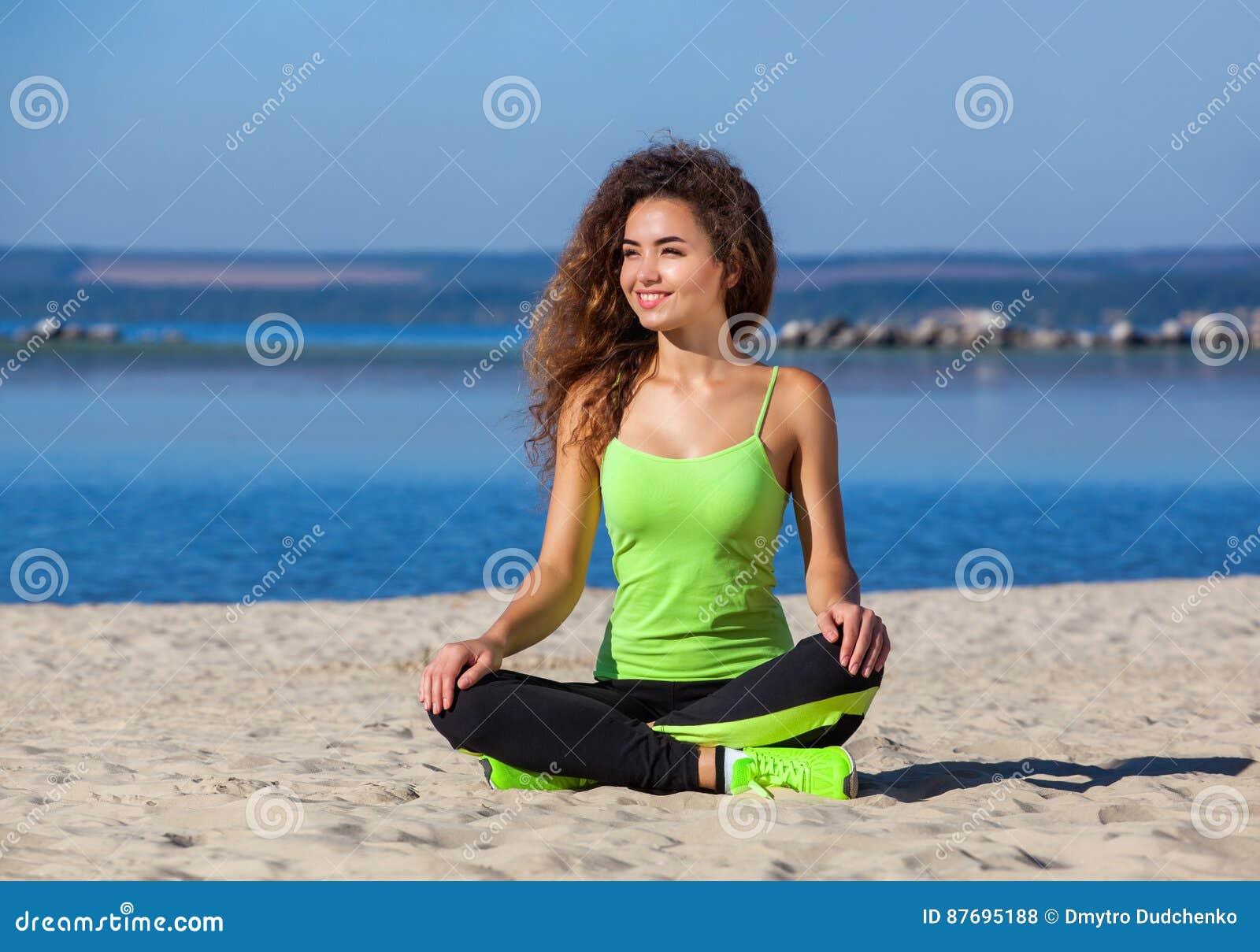 Potomstwa odchudzają dziewczyny z kędzierzawym włosy w czarnym i jasnozielonym tracksuit obsiadaniu po treningu w piasku na seash