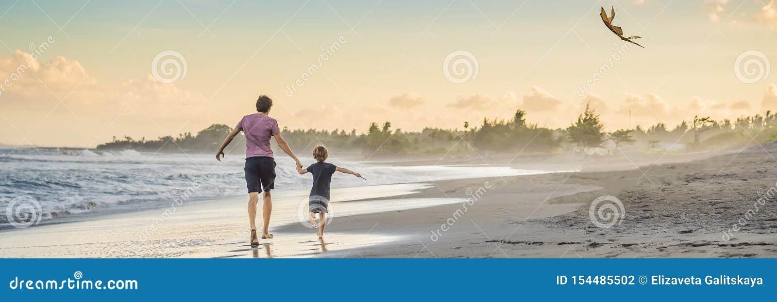 Potomstwa ojcują i jego syna bieg z kanią na plażowym sztandarze, DŁUGI format
