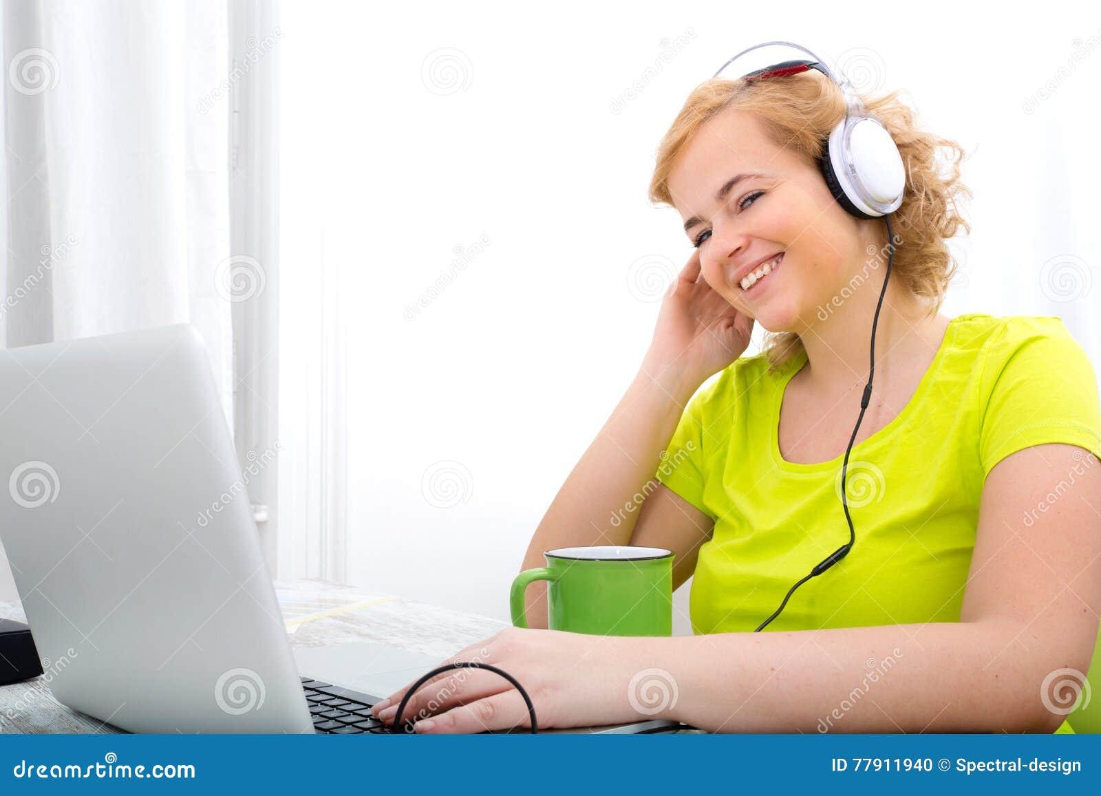 Potomstwa plus wielkościowa kobieta słucha audio podczas gdy pracujący na lapt
