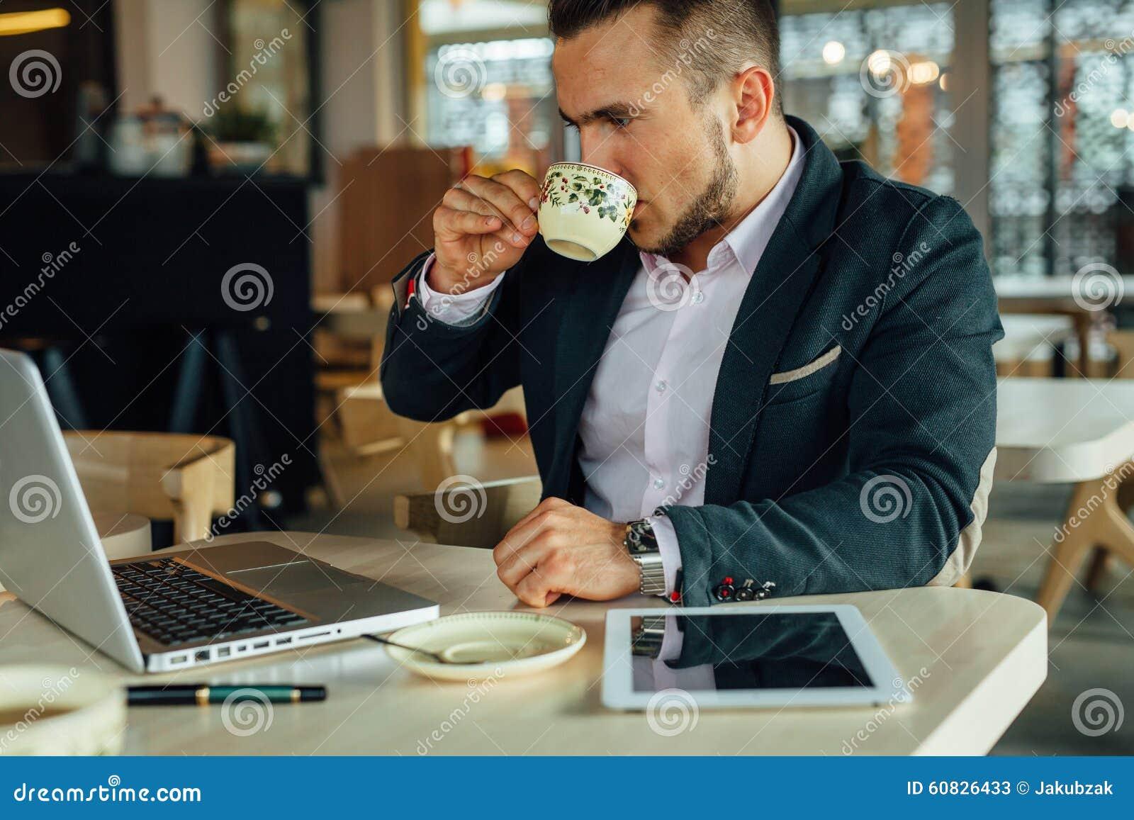 Potomstwa skupiali się biznesmena obsiadanie w café, pracuje na jego lapto