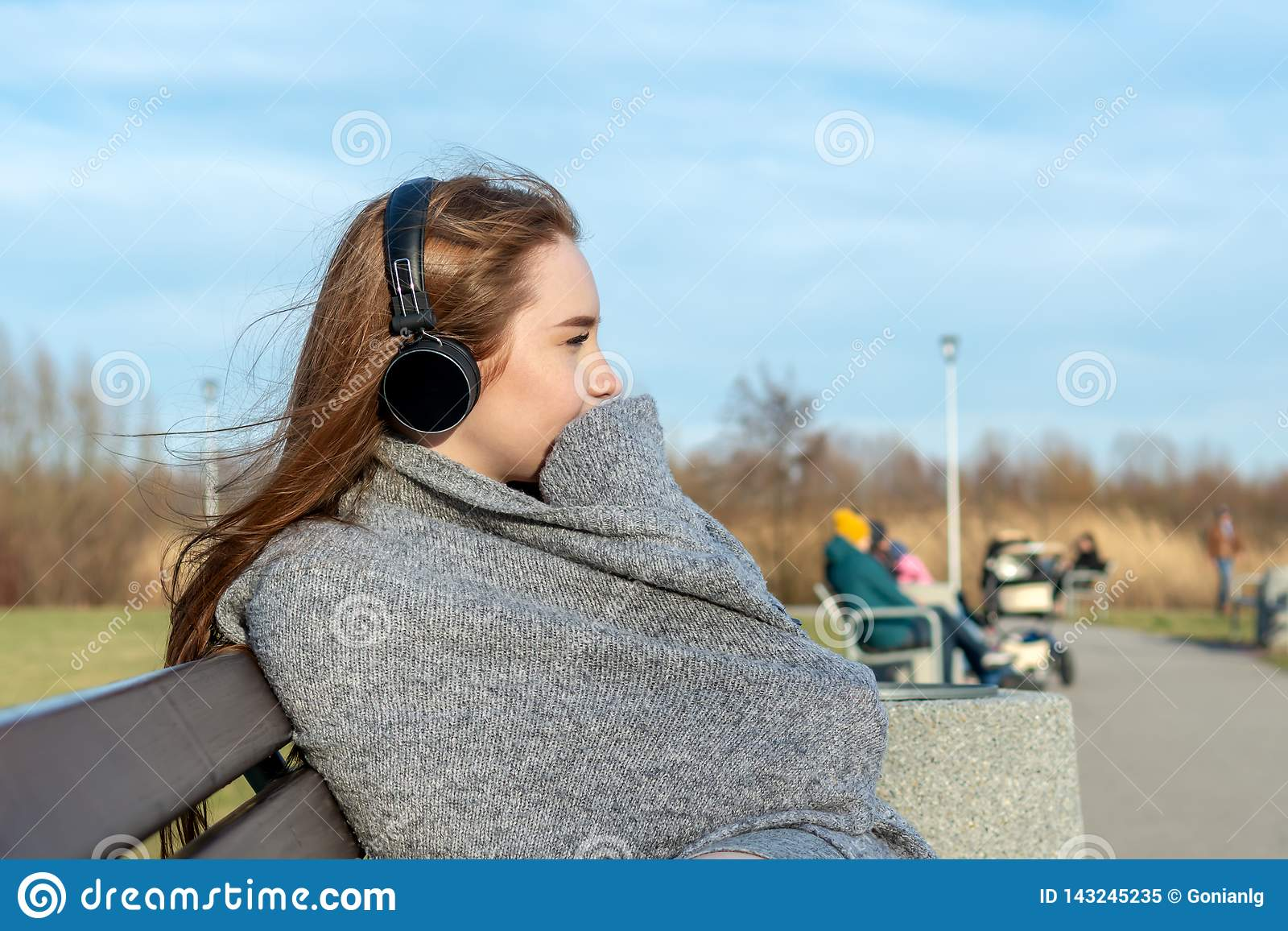 Potomstwa, szczęśliwa rudzielec dziewczyna w wiośnie w parku blisko rzeki słuchają muzyka przez bezprzewodowych bluetooth hełmofo