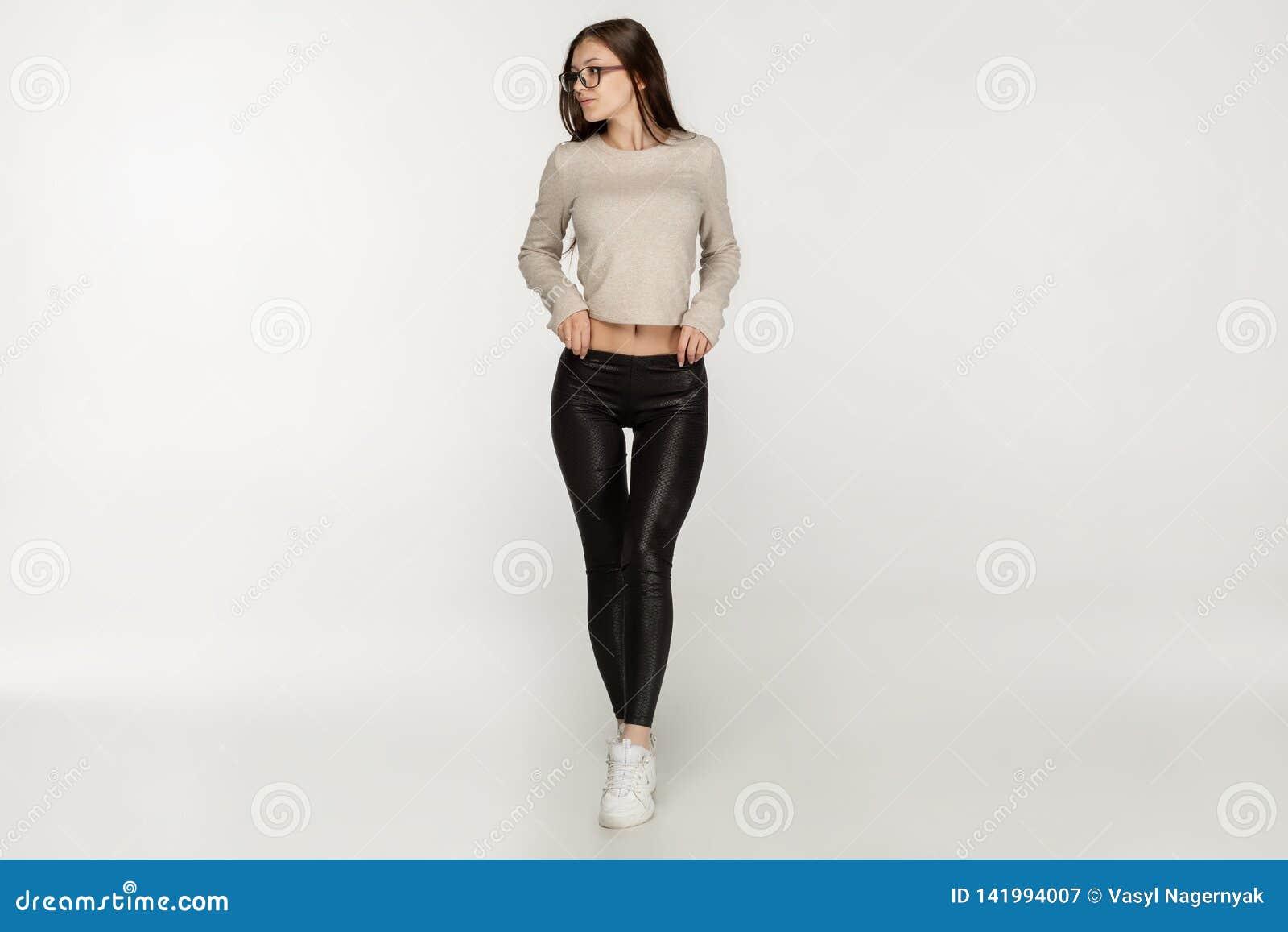 Potomstwa tęsk z włosami brunetki dziewczyna jest ubranym czarnych legginds w okularach przeciwsłonecznych