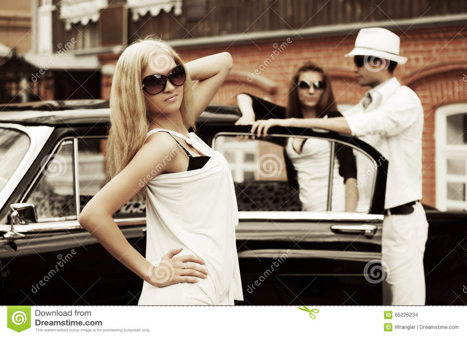 Potomstwo mody kobieta w okularach przeciwsłonecznych obok retro samochodu