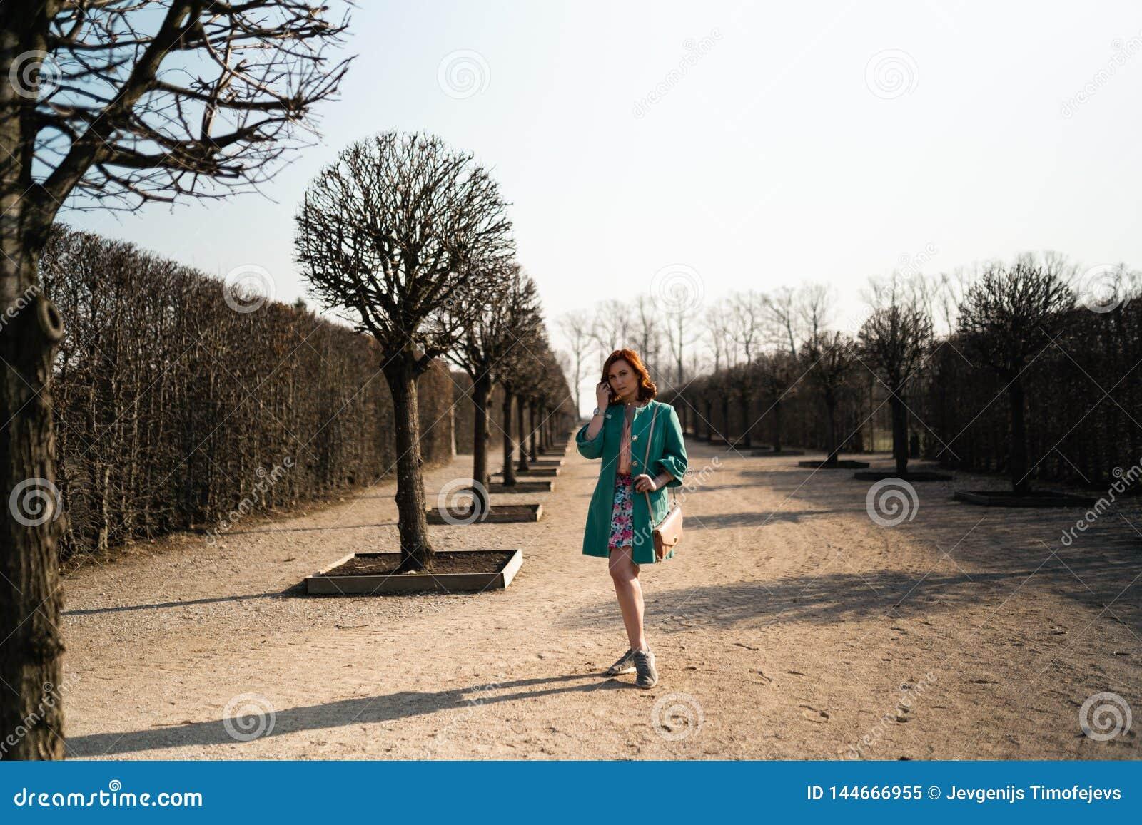 Potomstwo mody kochanka kobieta waling w parku jest ubranym żywą zieloną kurtkę i kolorową spódnicę