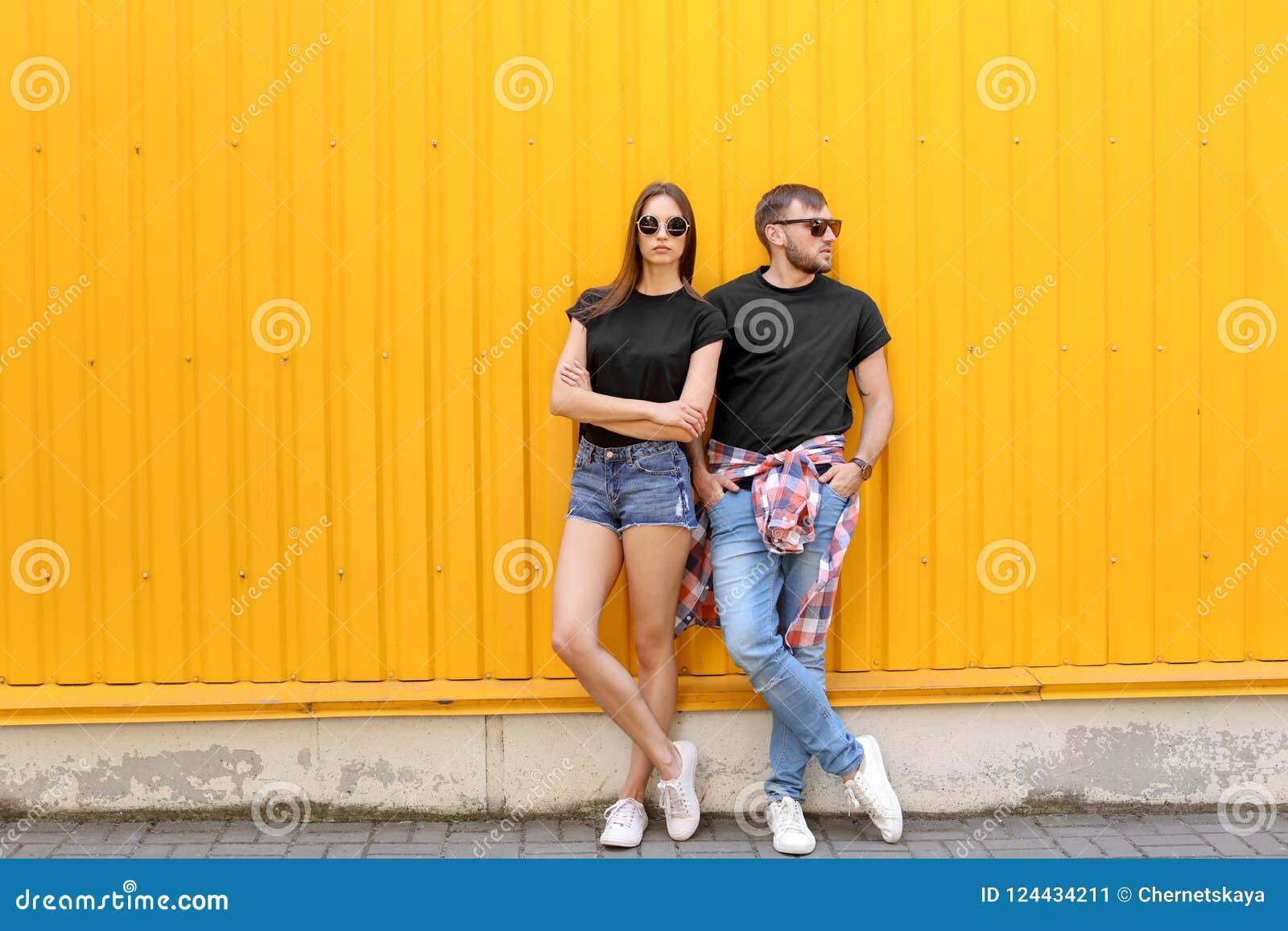 Potomstwo para jest ubranym czarne koszulki blisko barwi ścianę
