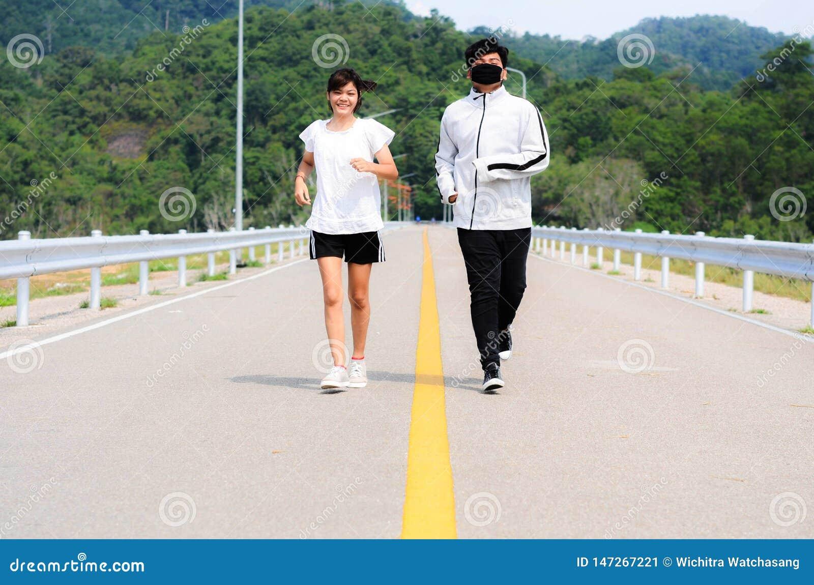 Potomstwo para jogging w parku zdrowie fizyczne fitness jogs pos?uchaj muzyki podczas gdy przeno?ne