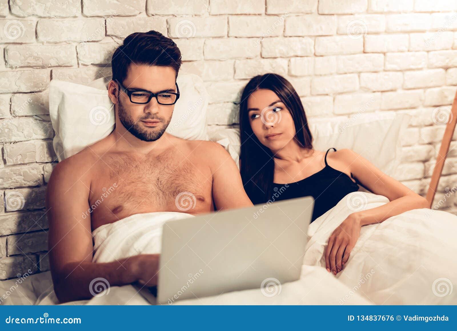 Potomstwo para w łóżku, mężczyzna Pracujący laptop Zanudzająca żona