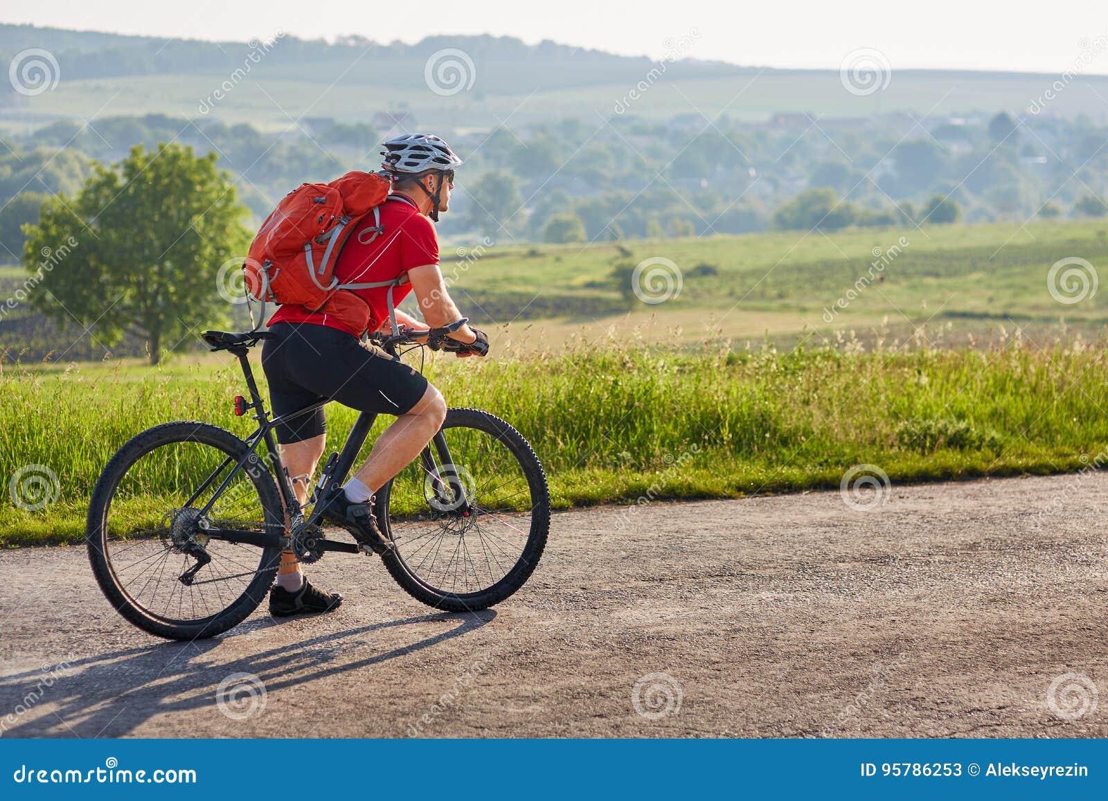 Potrtrait του ποδηλάτη σε έναν μακρύ δρόμο στην επαρχία ενάντια στο θερινό τοπίο