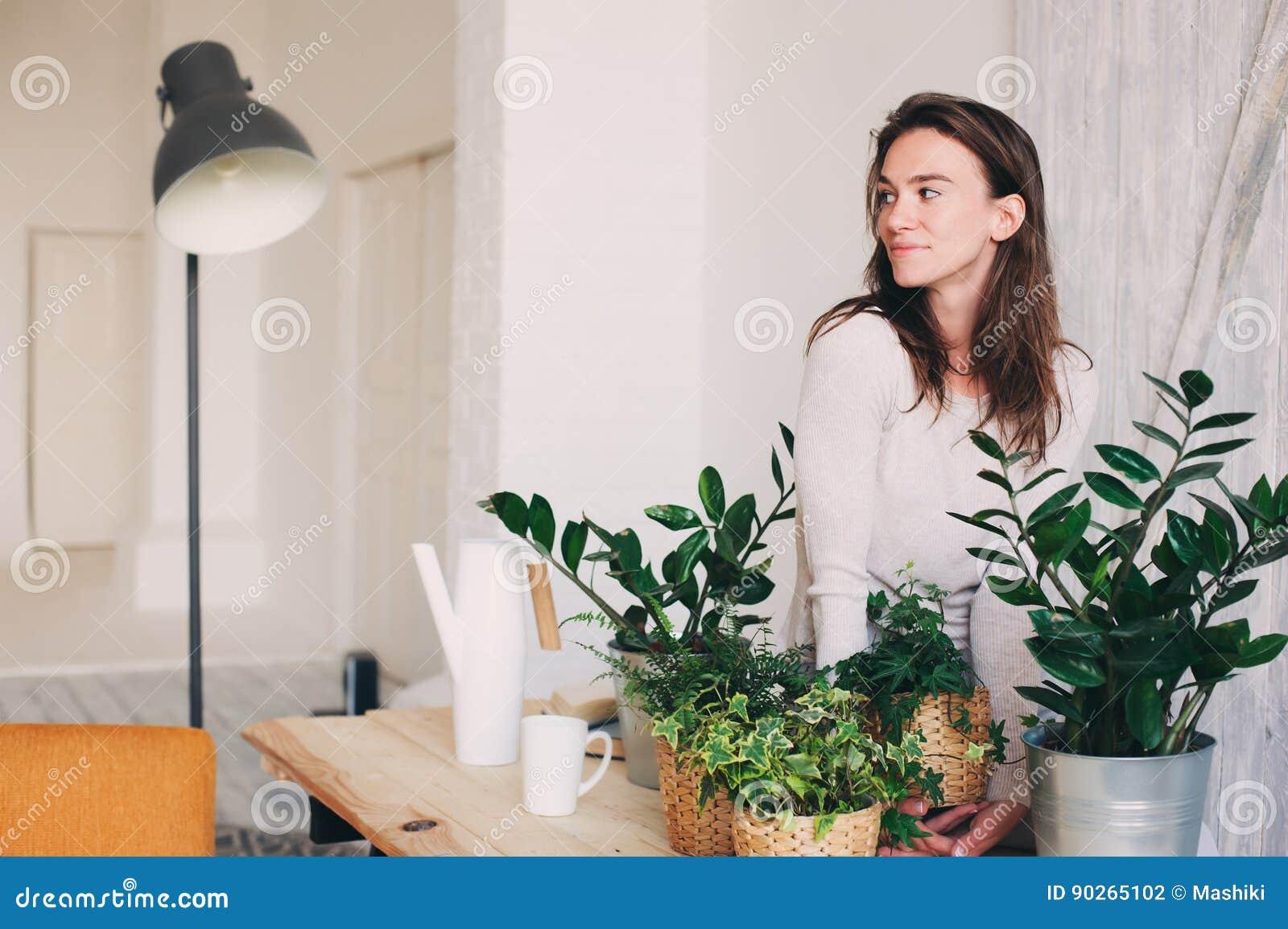 Pots de fleurs de arrosage de jeune femme à la maison Série occasionnelle de mode de vie dans l intérieur scandinave moderne
