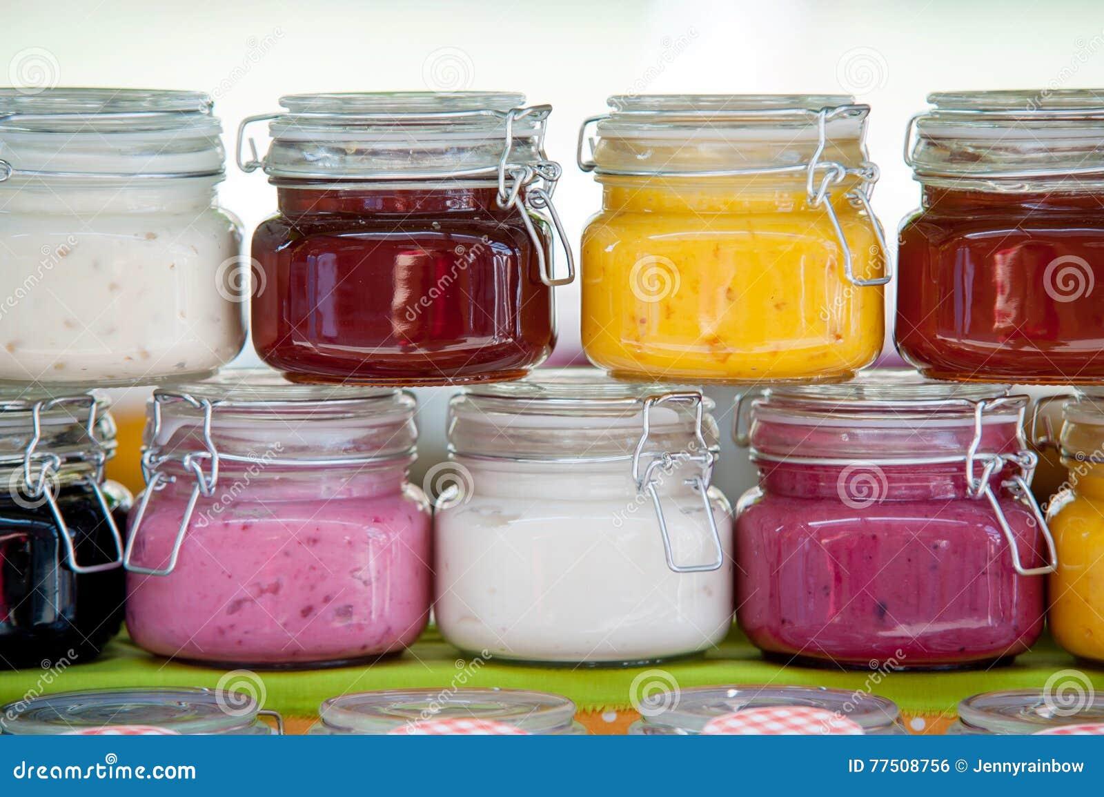 Pots en verre avec les confitures colorées dans une rangée