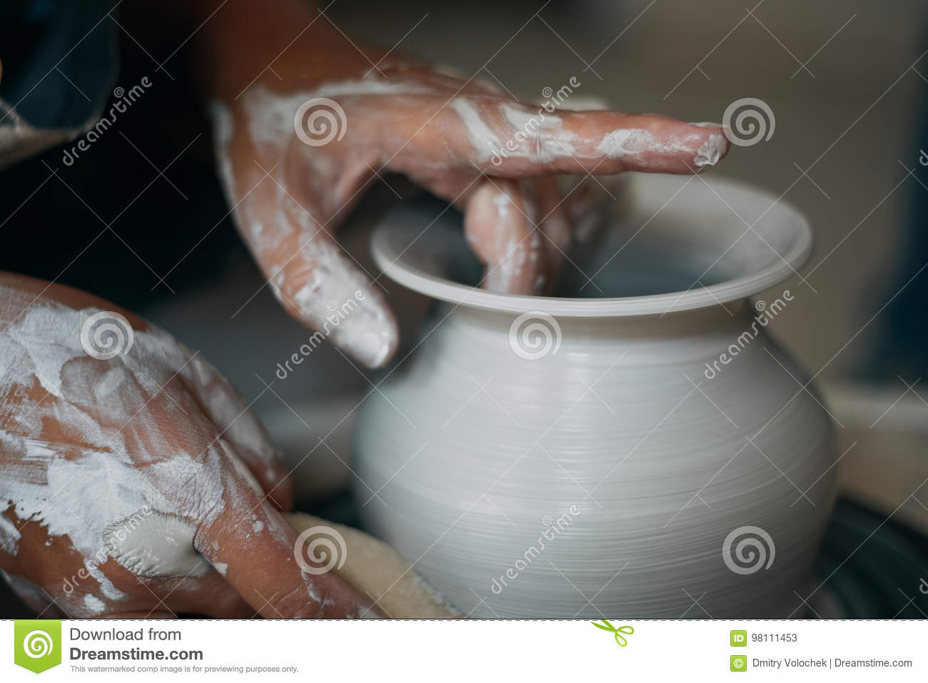 Potter works at pottery wheel, dirty woman hands