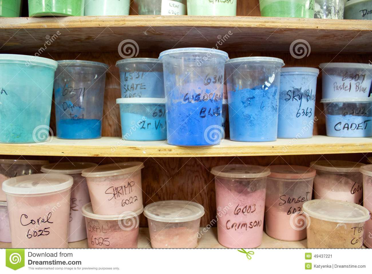 Pottery glaze in different colours in plastic containers on shelves