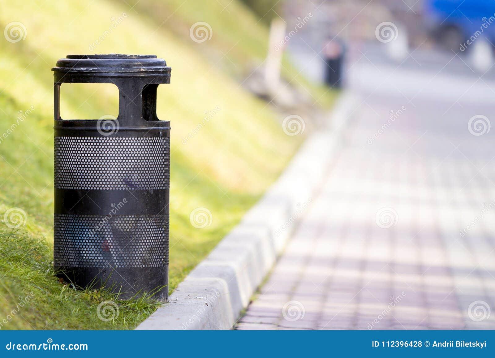 Poubelle de déchets noire en métal en parc avec le fond ensoleillé brouillé
