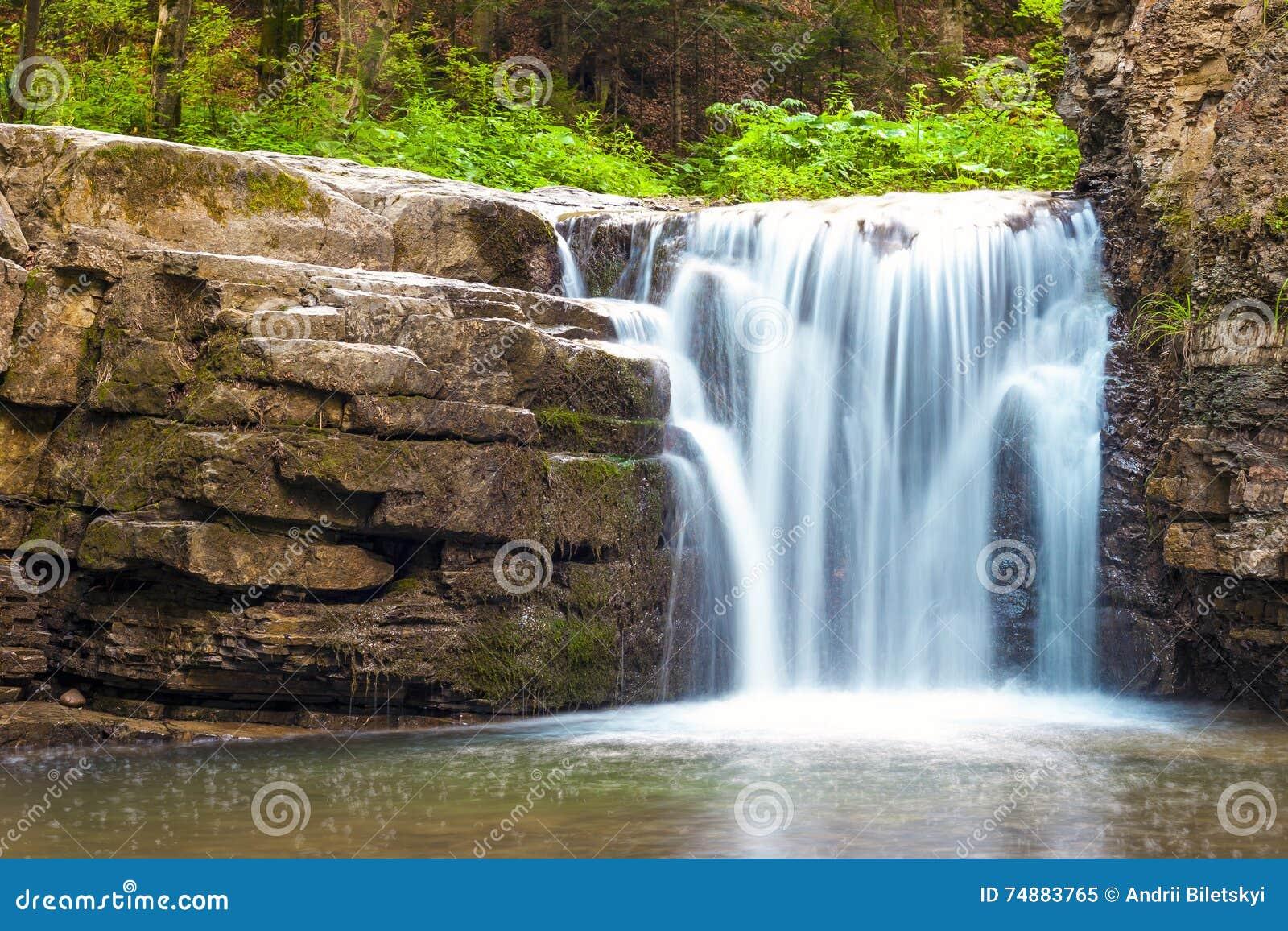 Pouca cachoeira na floresta da montanha com água de formação de espuma de seda