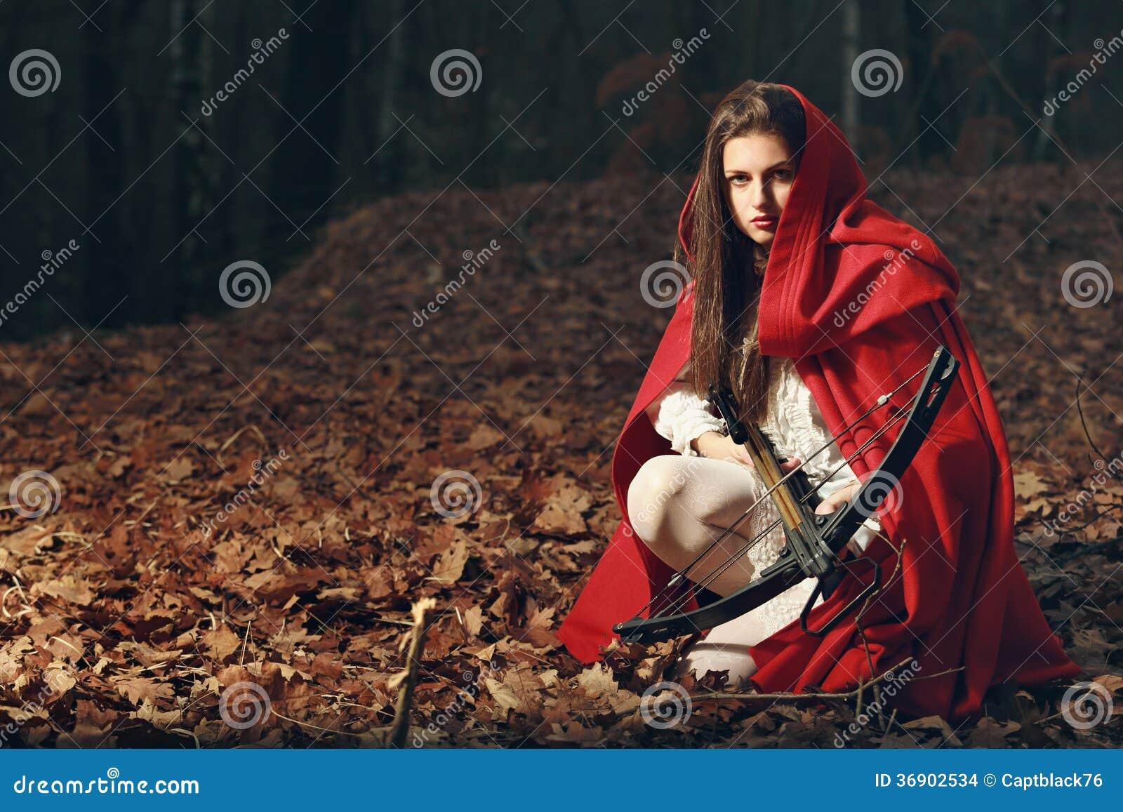 Pouca capa de equitação vermelha na floresta escura
