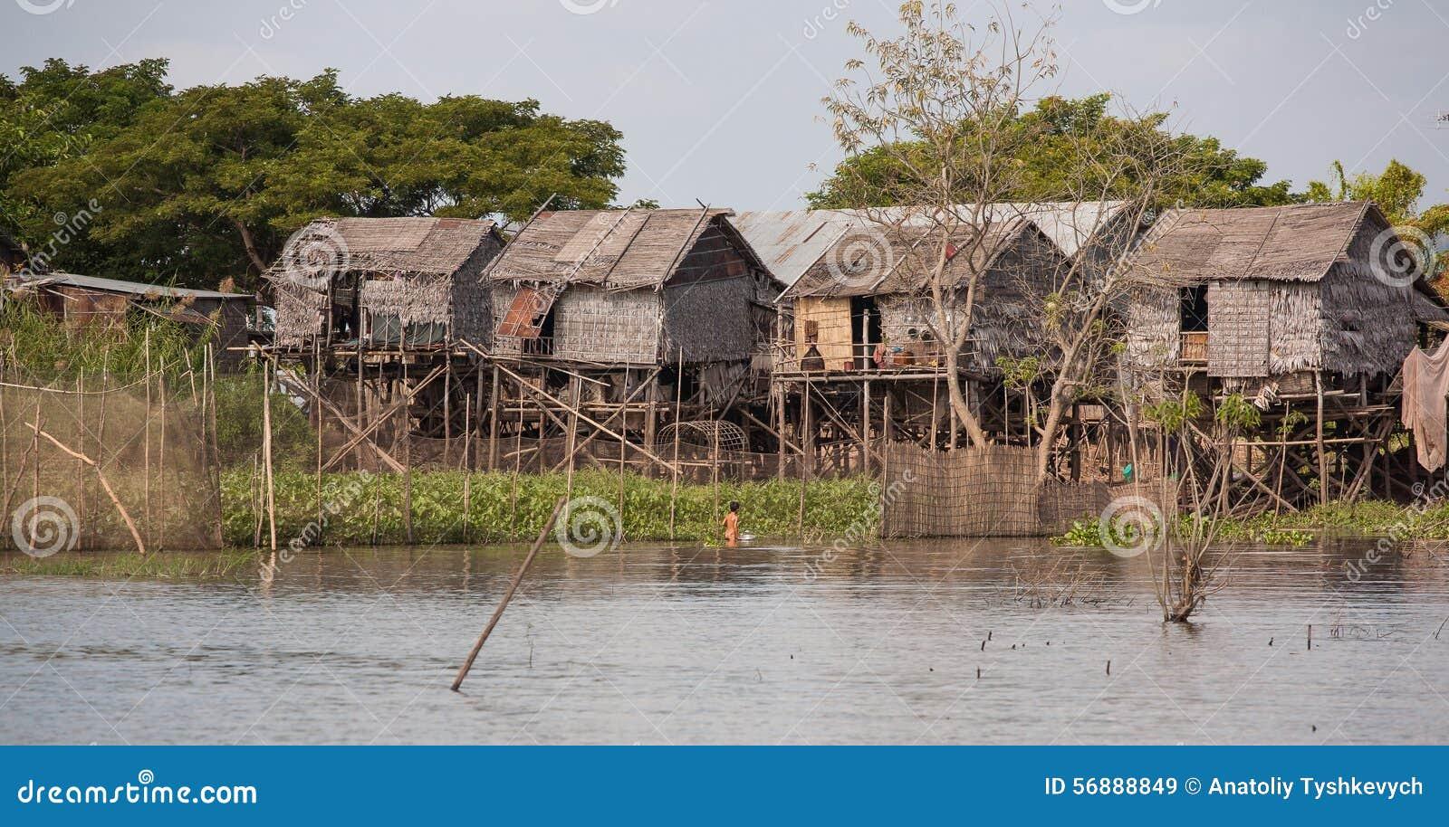 Pouca casa na água, uma pesca da criança com uma bacia do ferro