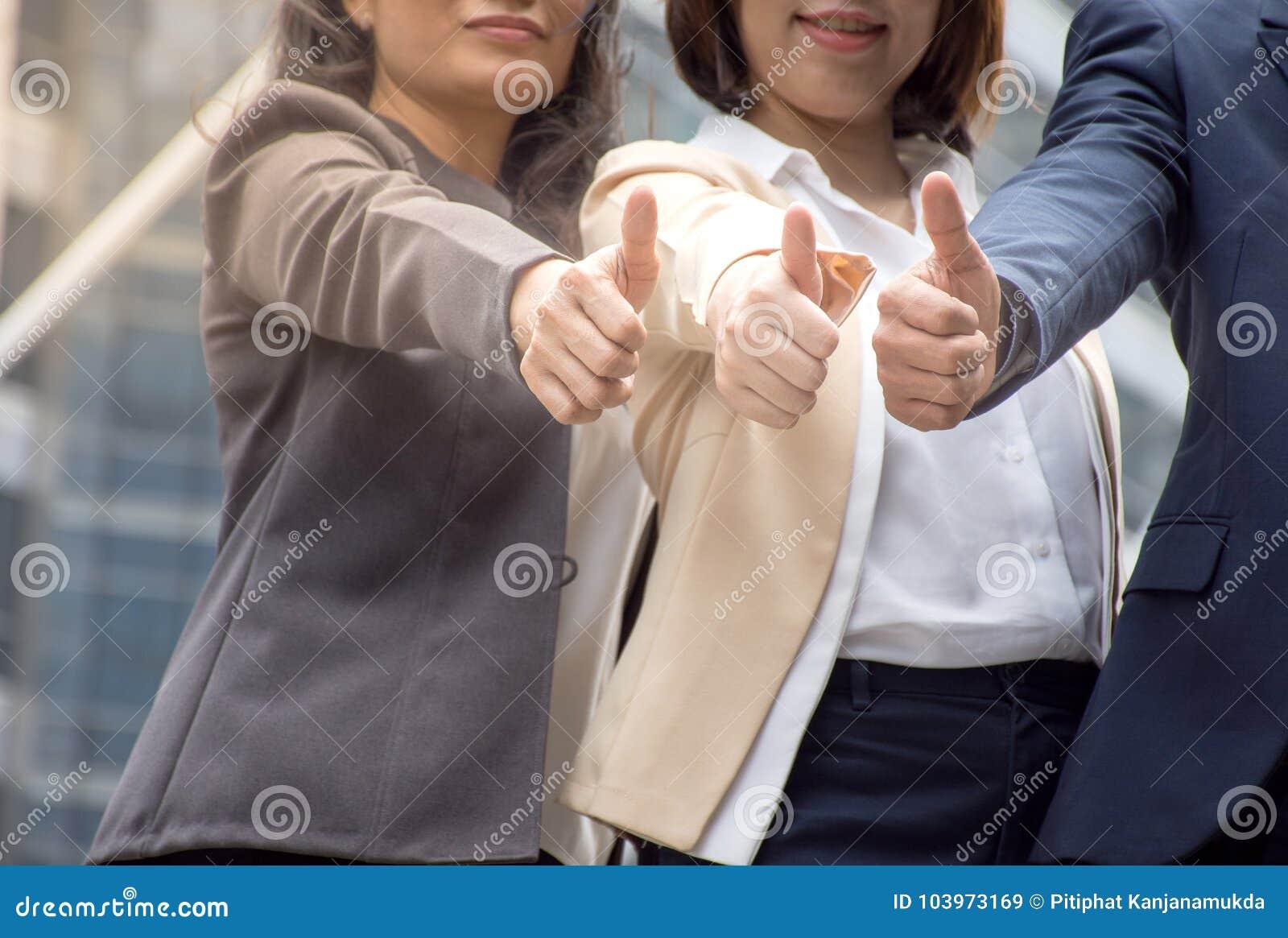 Pouce asiatique d équipe d affaires pour le bons travail/succès du travail d équipe