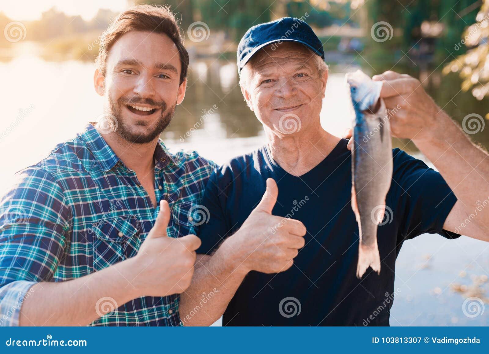 Pouces vers le haut Un homme se tient à côté d un vieil homme qui tient un poisson qu il a juste pêché