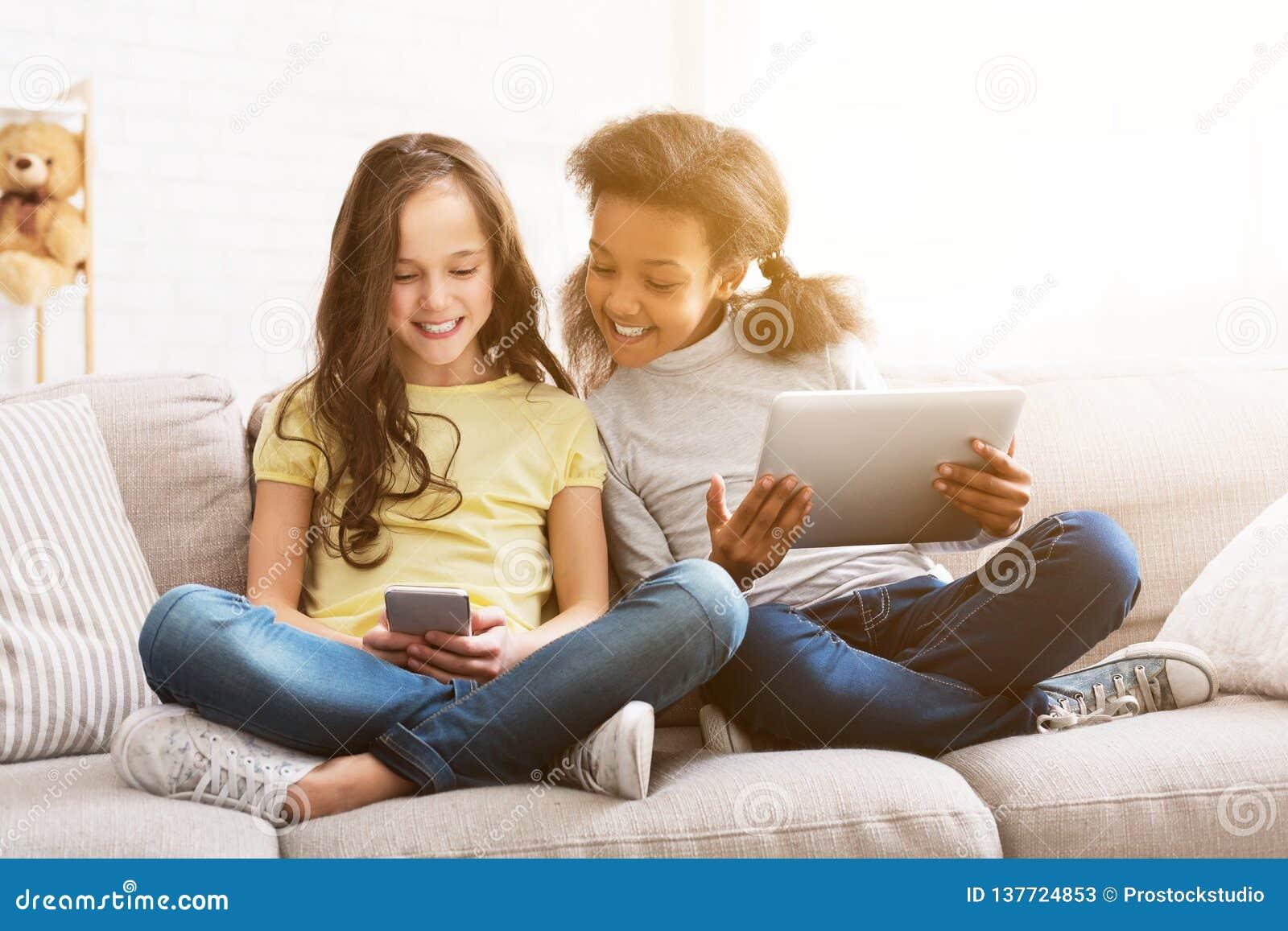 Pouco amigos com os dispositivos que sentam-se no sofá em casa