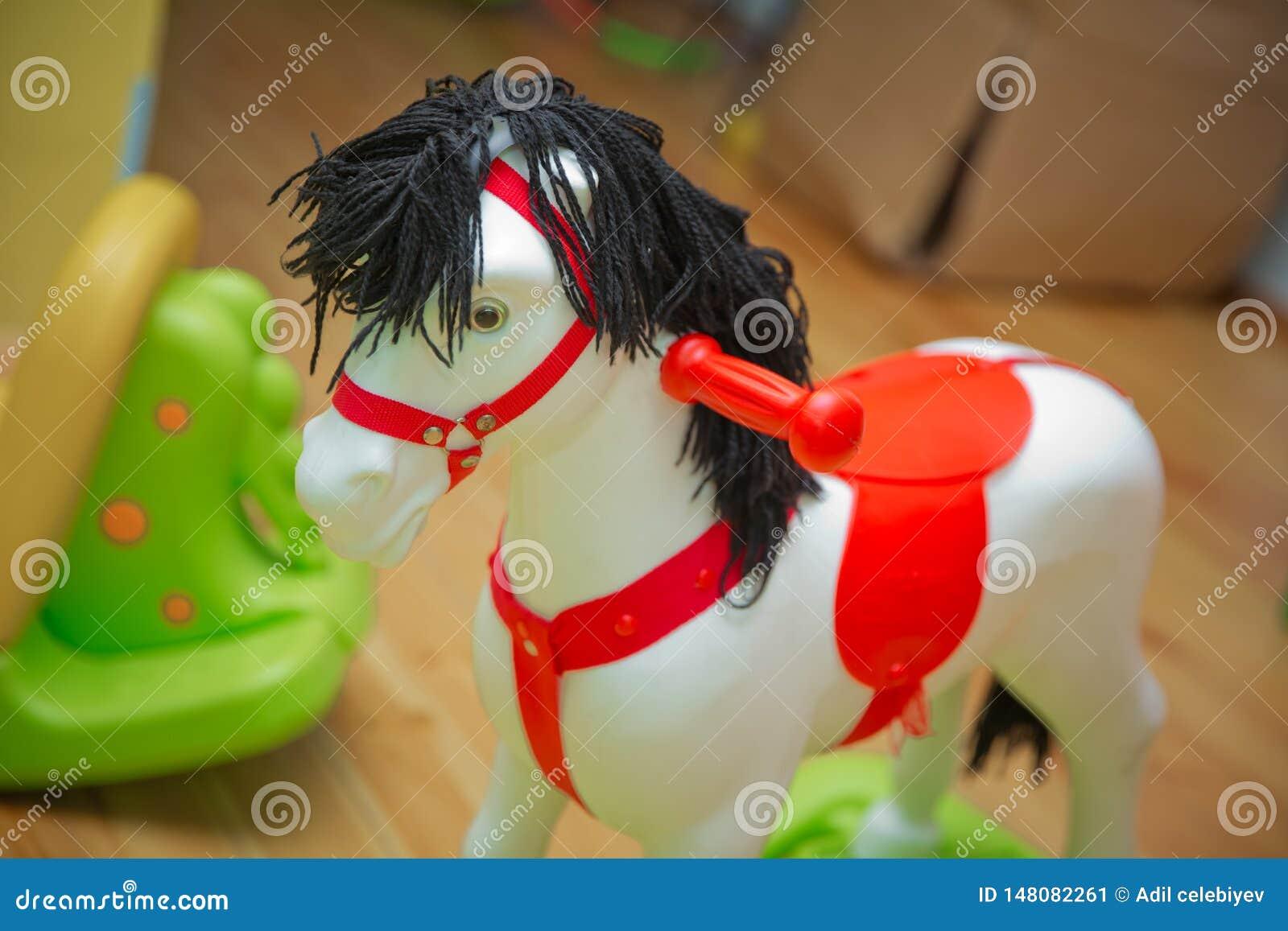 Pouco boneca branca do balanço do balancim do pônei em um assoalho de madeira Cavalo do balanço com correia de couro em um assoal