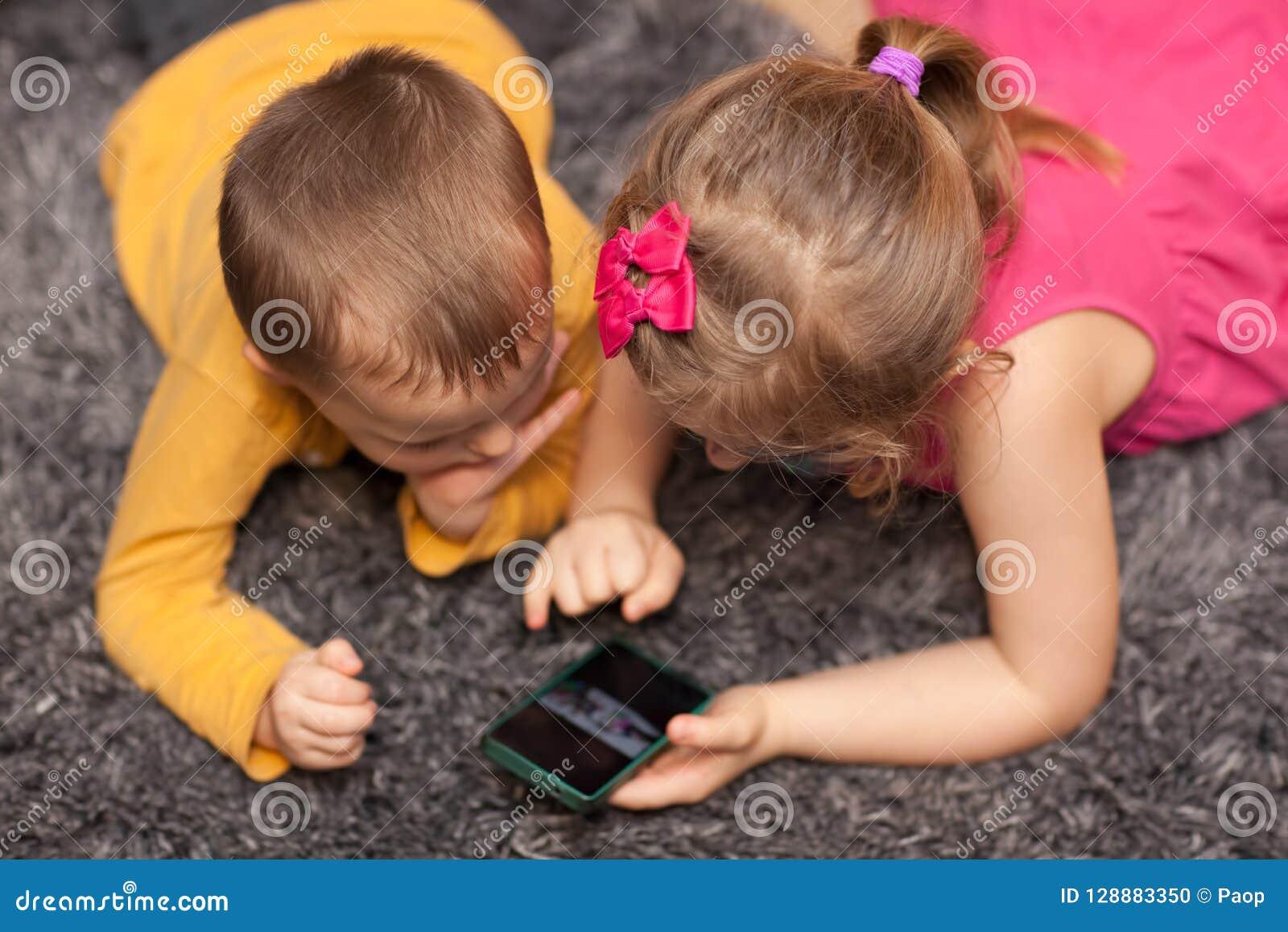 Pouco crianças que usam o smartphone em casa
