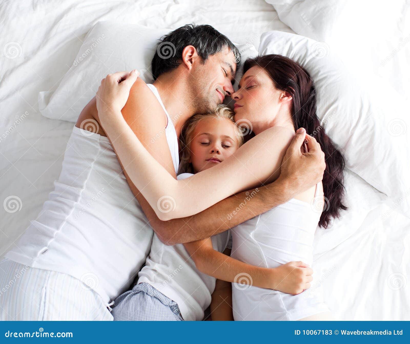 Pouco gril que dorme na cama com seus pais