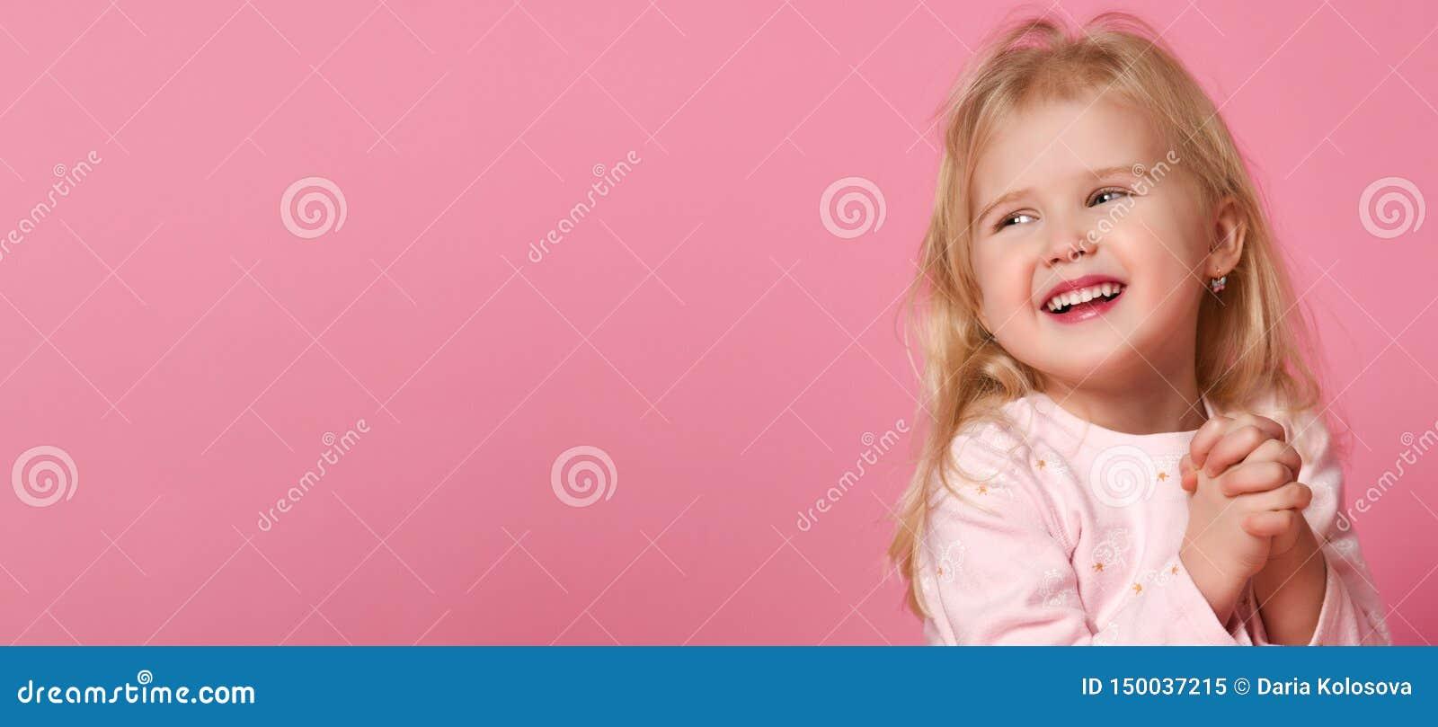 Pouco louro bonito da crian?a da menina em um terno cor-de-rosa ? t?mido em um fundo cor-de-rosa