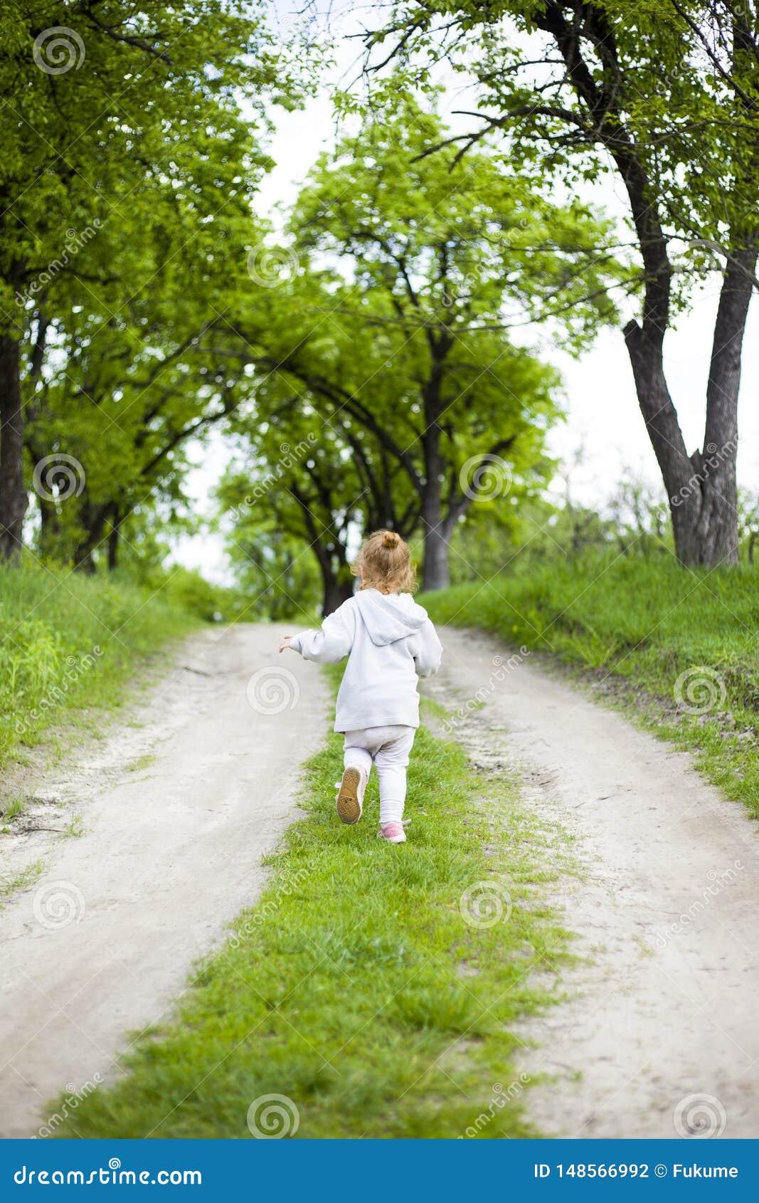 Pouco menina bonito do ruivo corre ao longo de uma estrada de terra com grama e risos