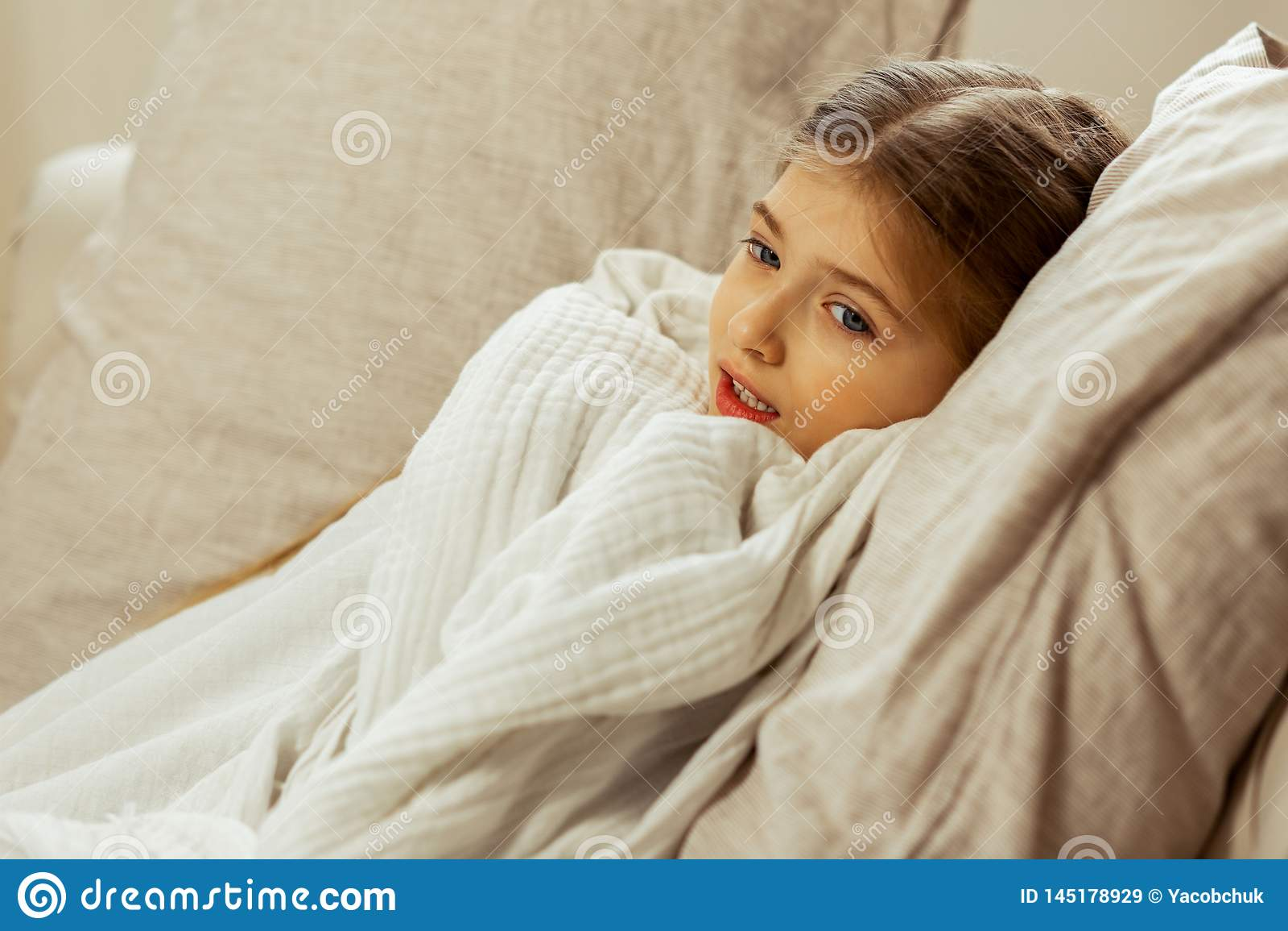 Pouco menina doente envolveu em uma cobertura que encontra-se na cama