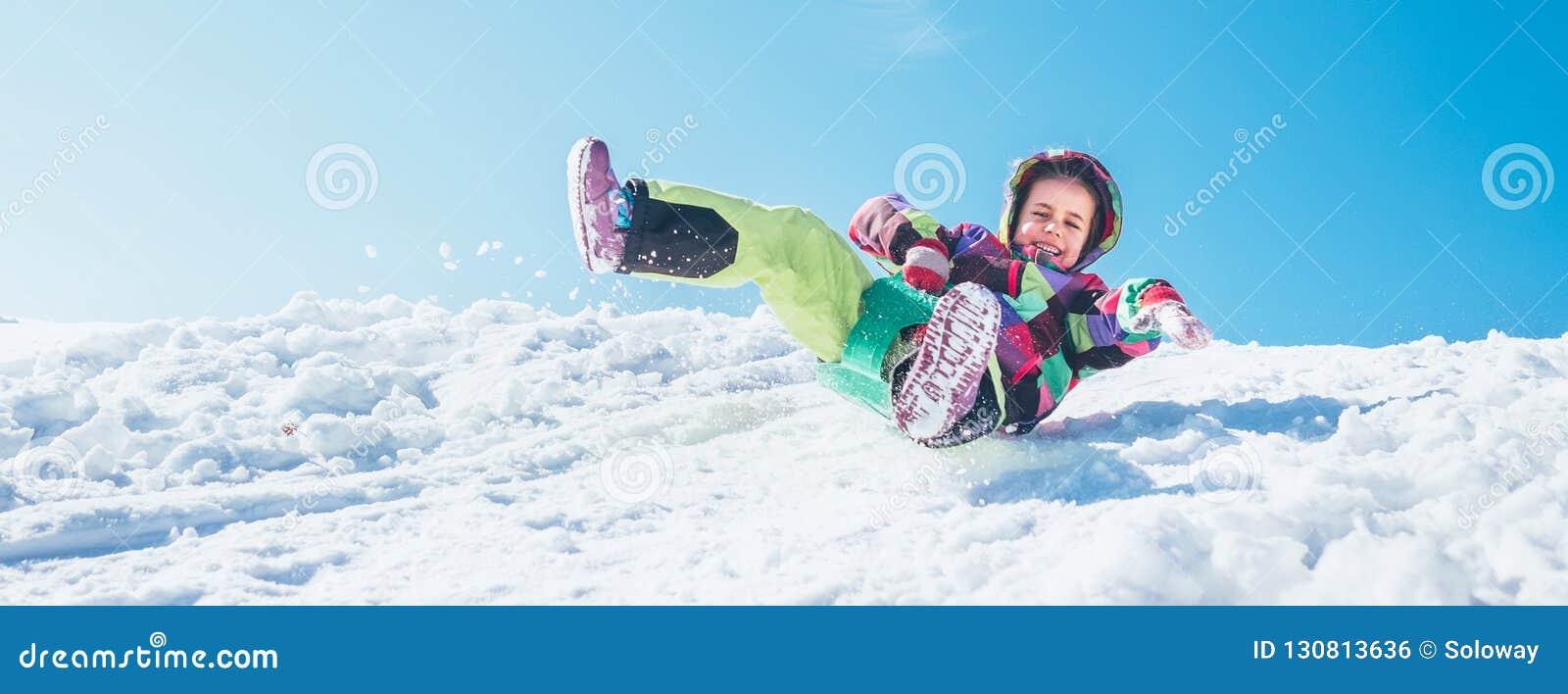 Pouco menina feliz desliza para baixo da inclinação da neve com céu azul