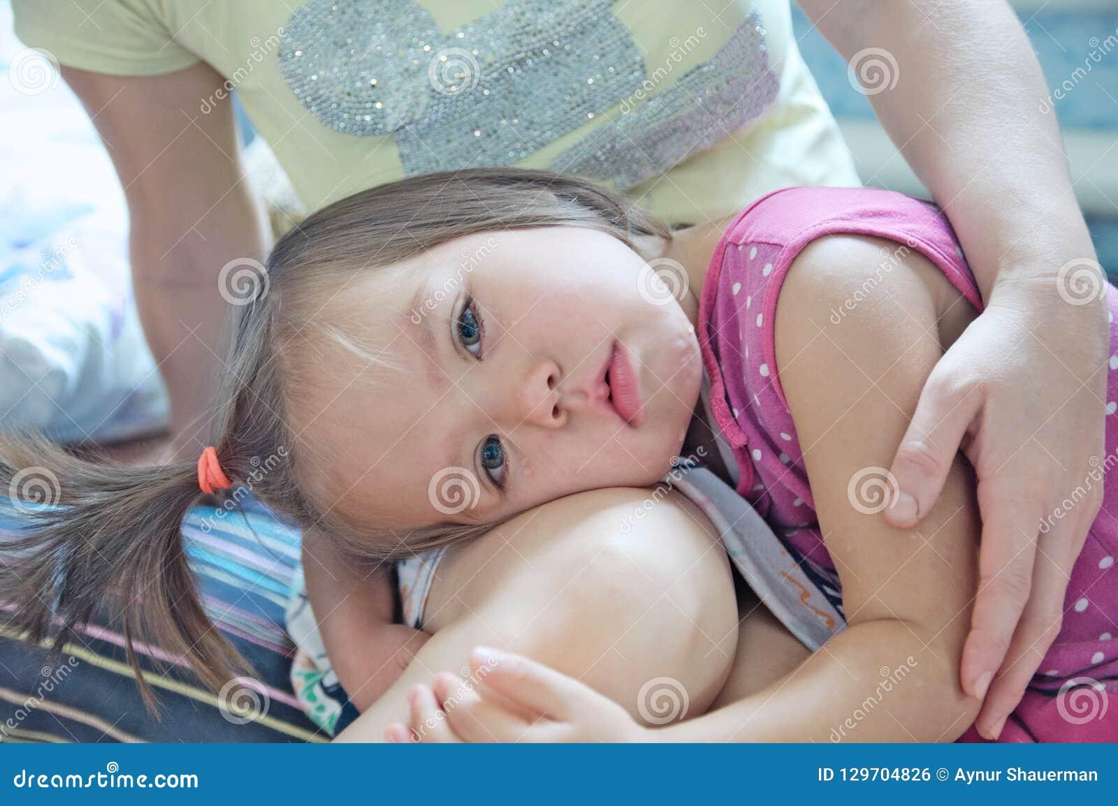 Pouco menina triste em joelhos das mães Menina de grito da terra arrendada da mãe acalmando para baixo a criança Chorar do rasgo