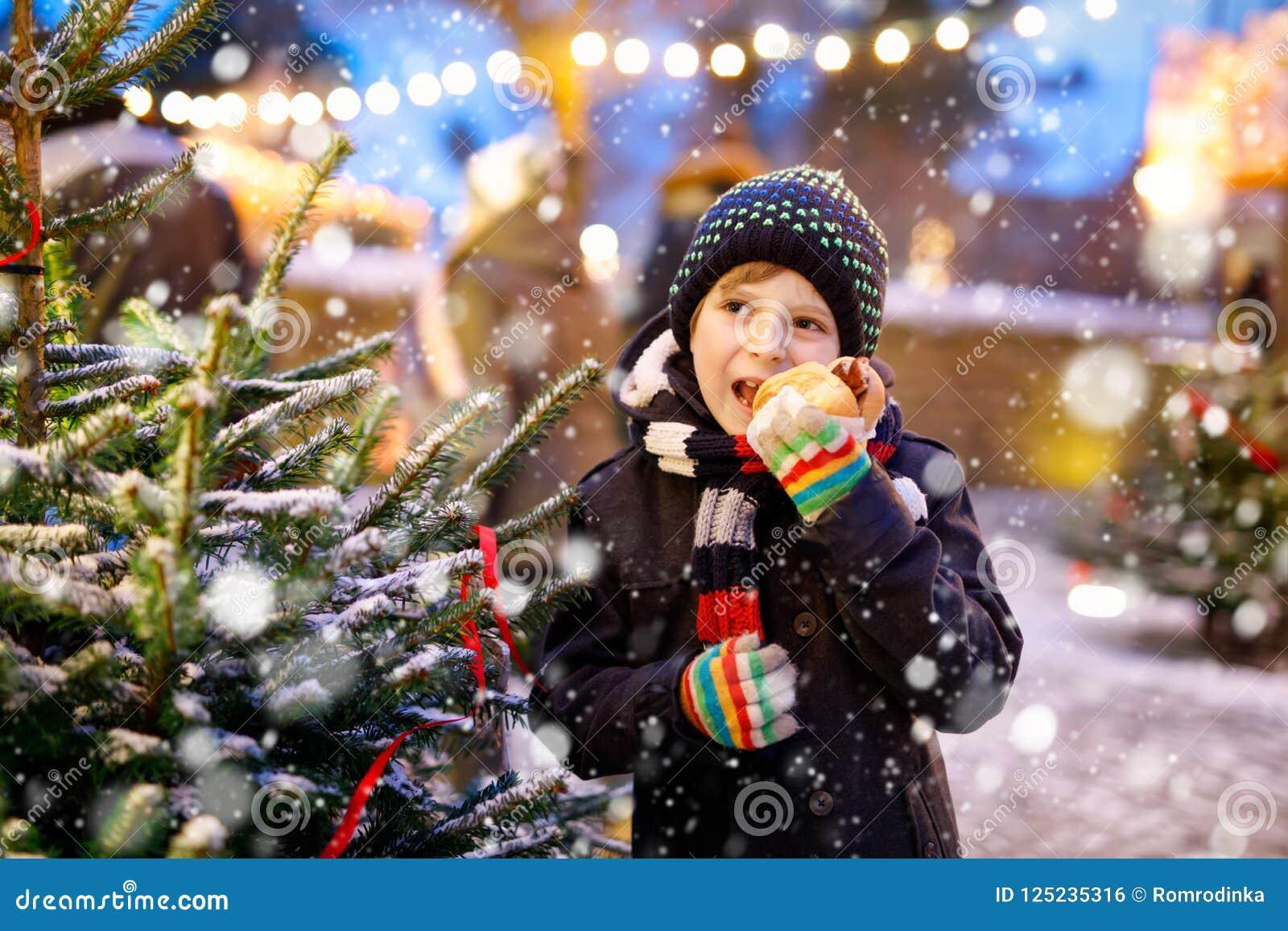 Pouco menino bonito da criança que come a salsicha alemão e que bebe o perfurador quente das crianças no mercado do Natal Criança