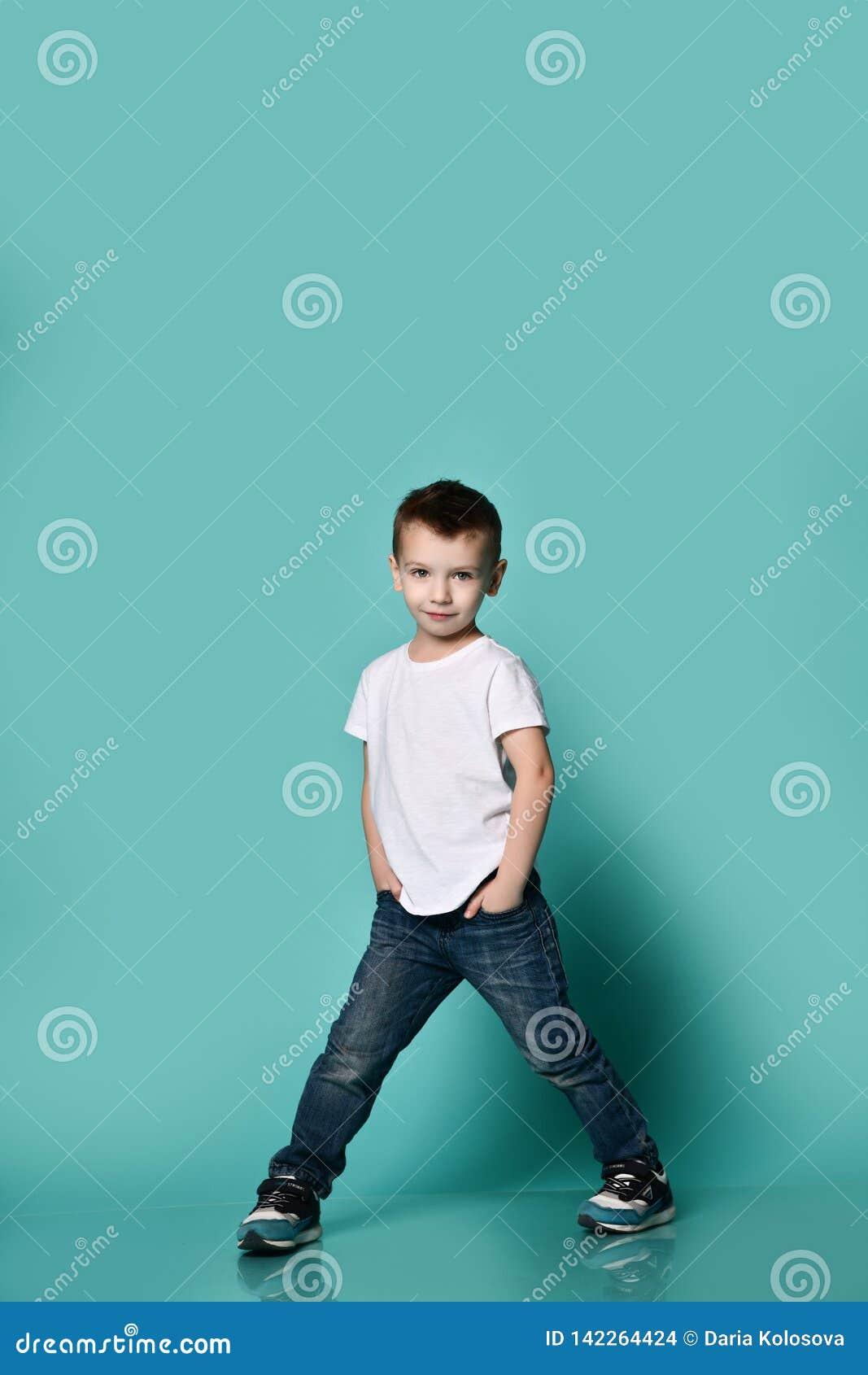 Pouco menino elegante que levanta na frente da parede azul