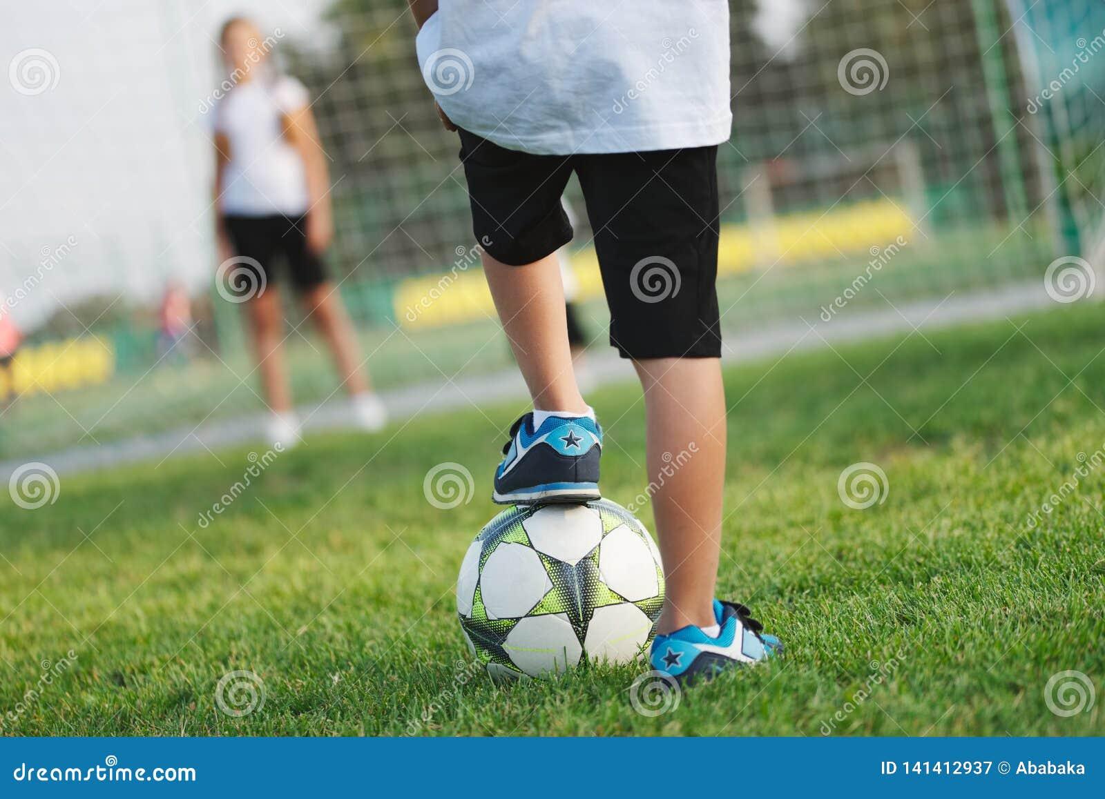 Pouco menino feliz no campo de futebol