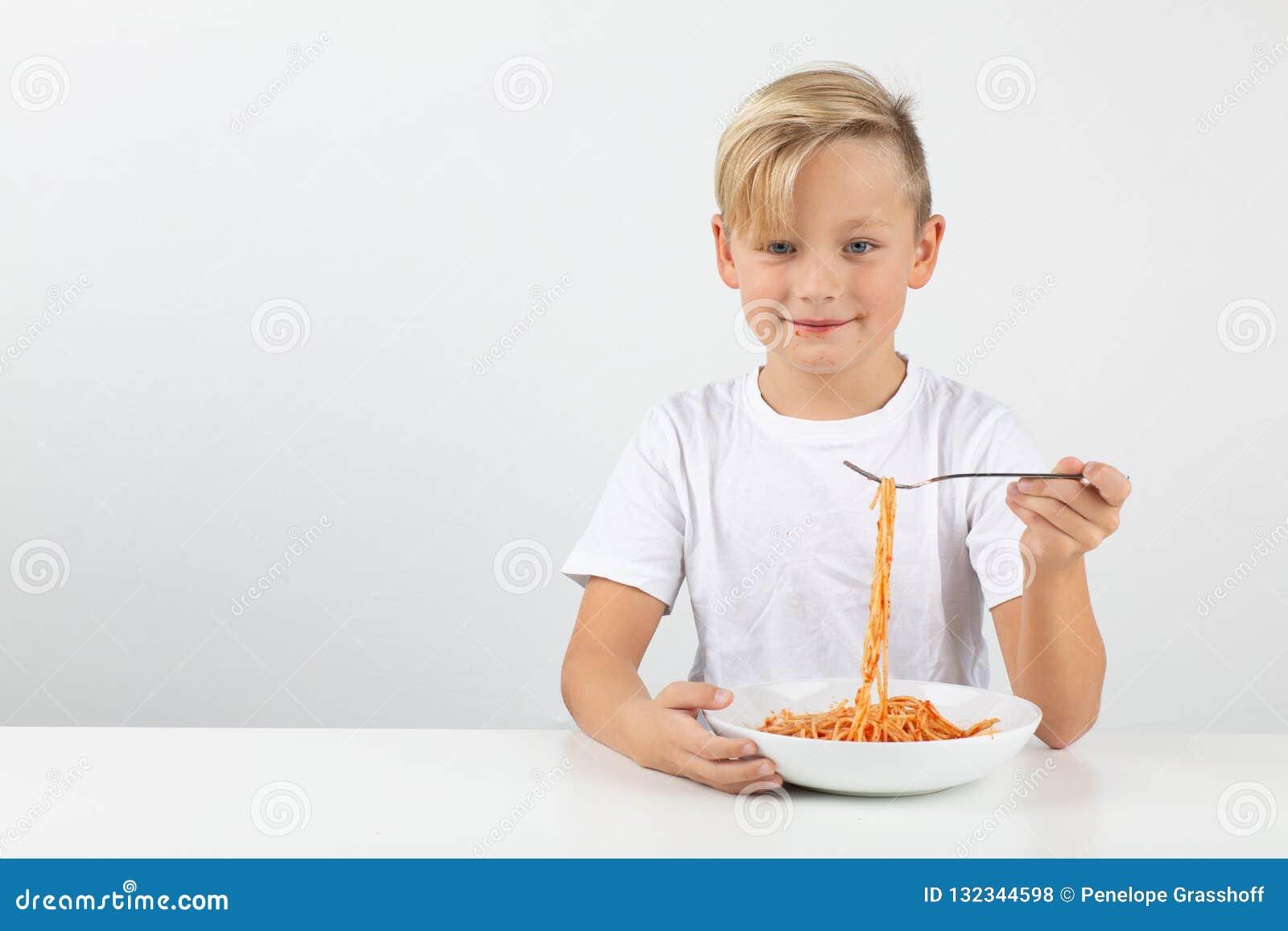 Pouco menino louro come os espaguetes e os sorrisos