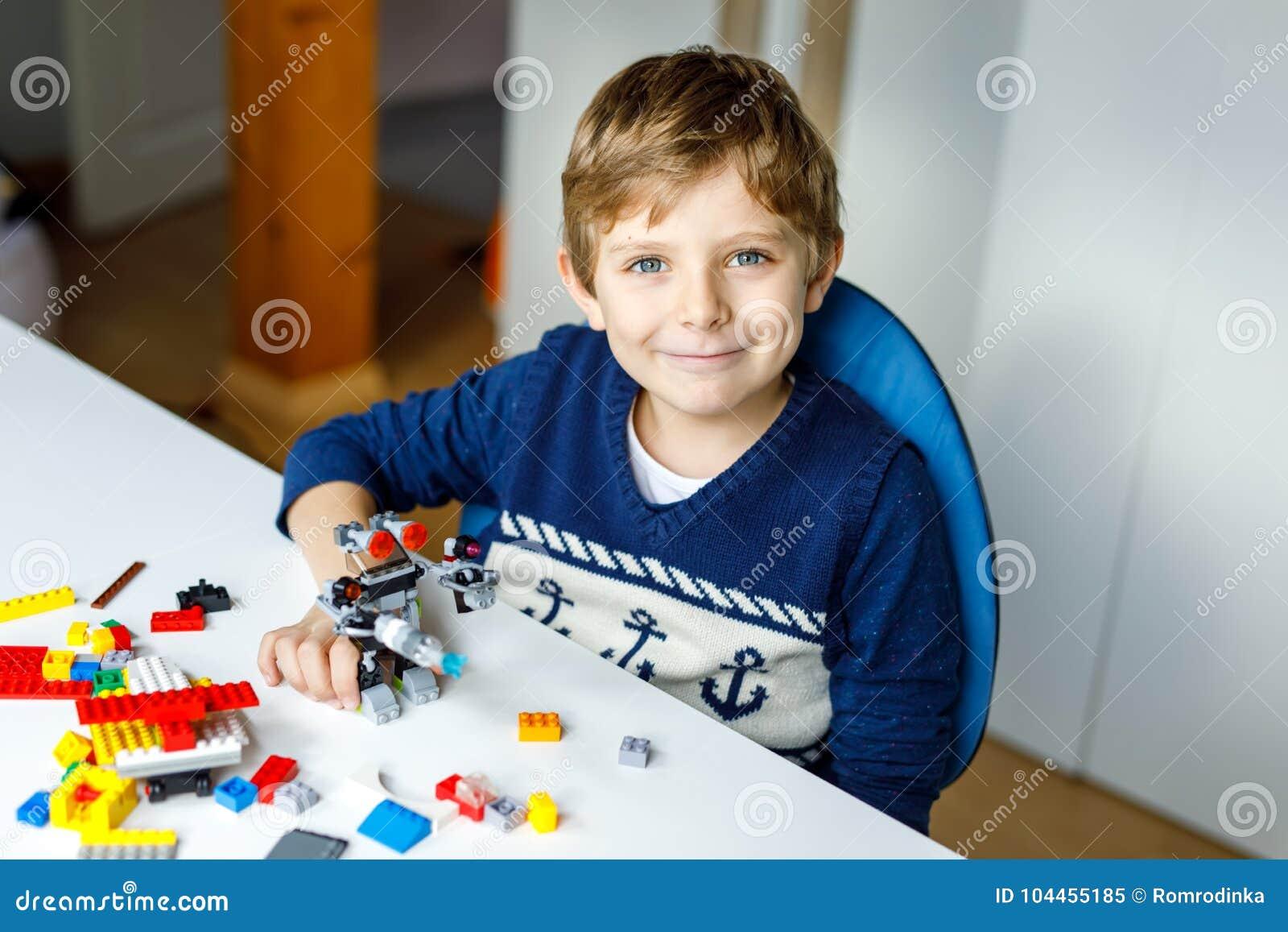 Pouco menino louro da criança que joga com lotes de blocos plásticos coloridos