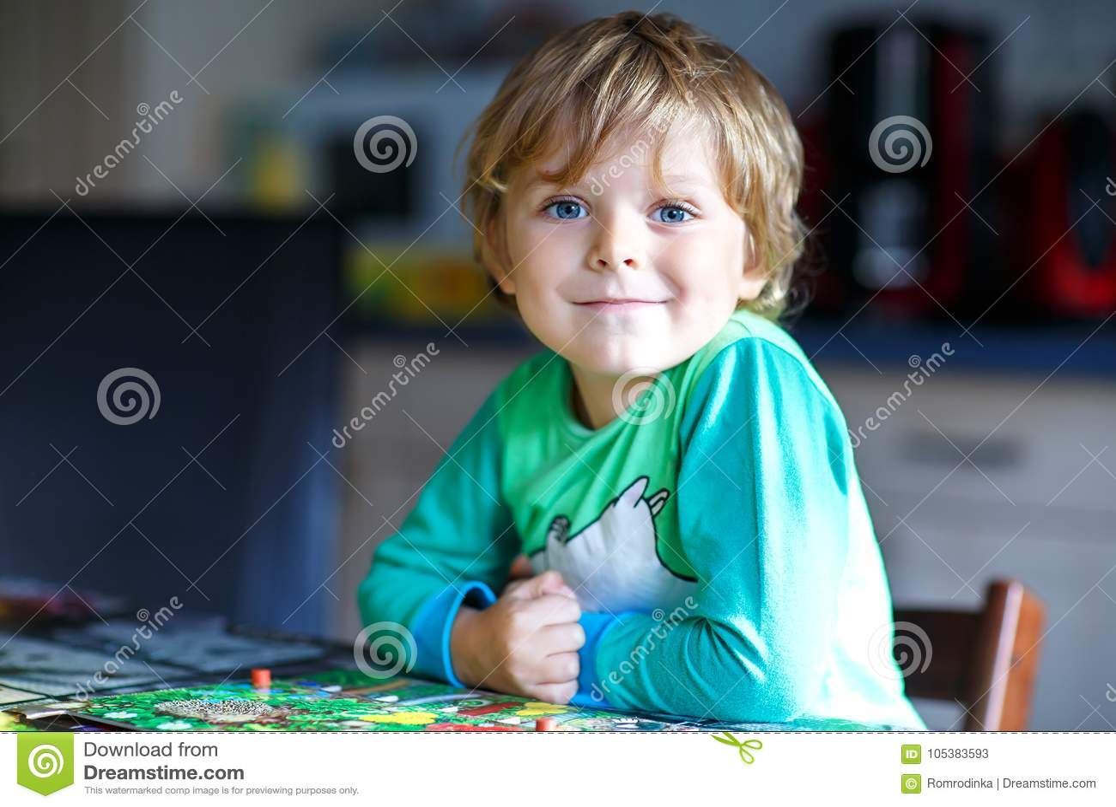 Pouco menino louro da criança que joga junto o jogo de mesa em casa Criança engraçada que tem o divertimento