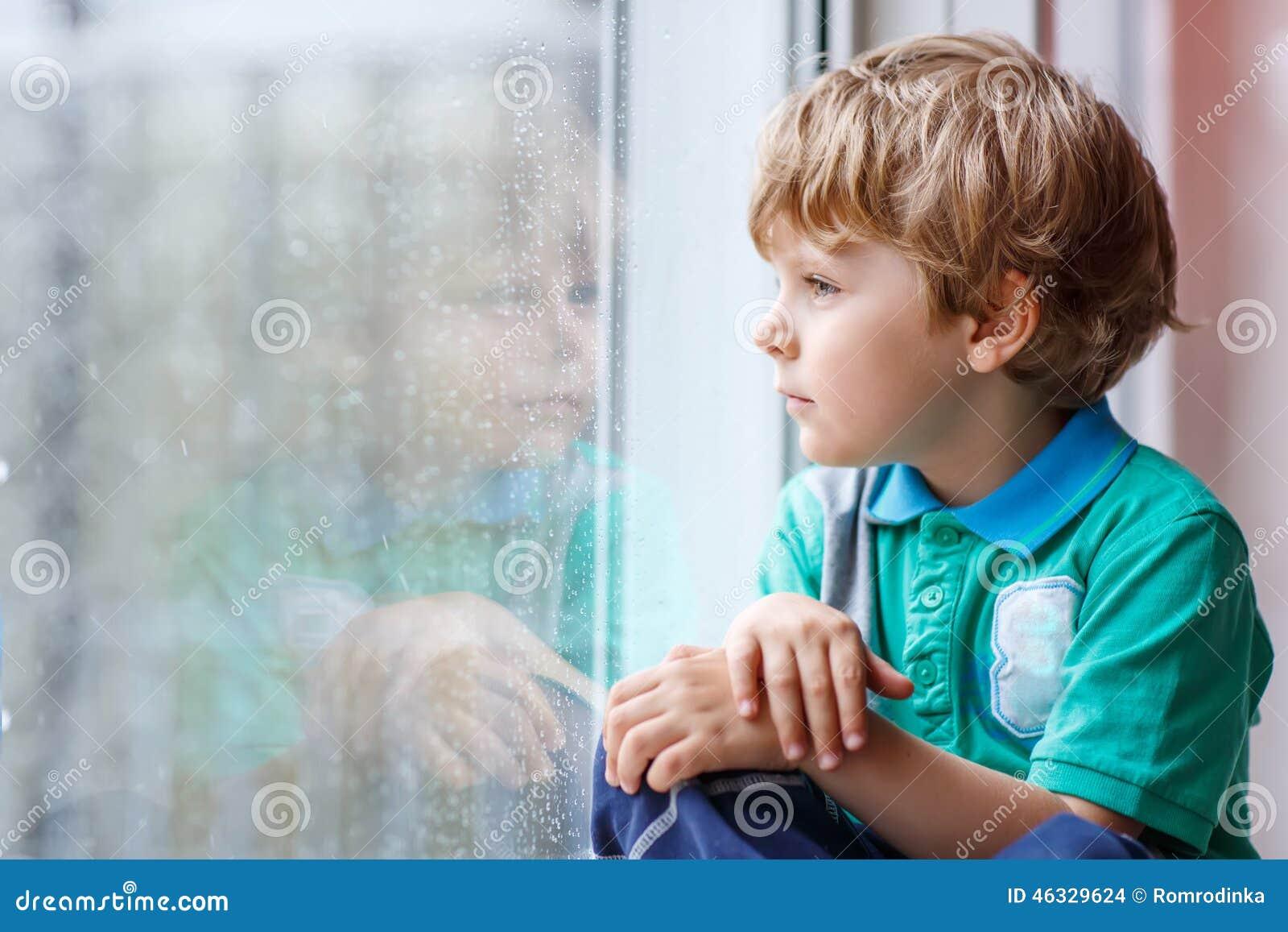 Pouco menino louro da criança que senta-se perto da janela e que olha no pingo de chuva