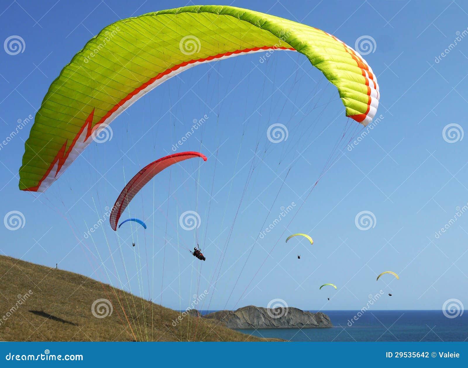 Poucos paragliders sobem sobre a costa de mar