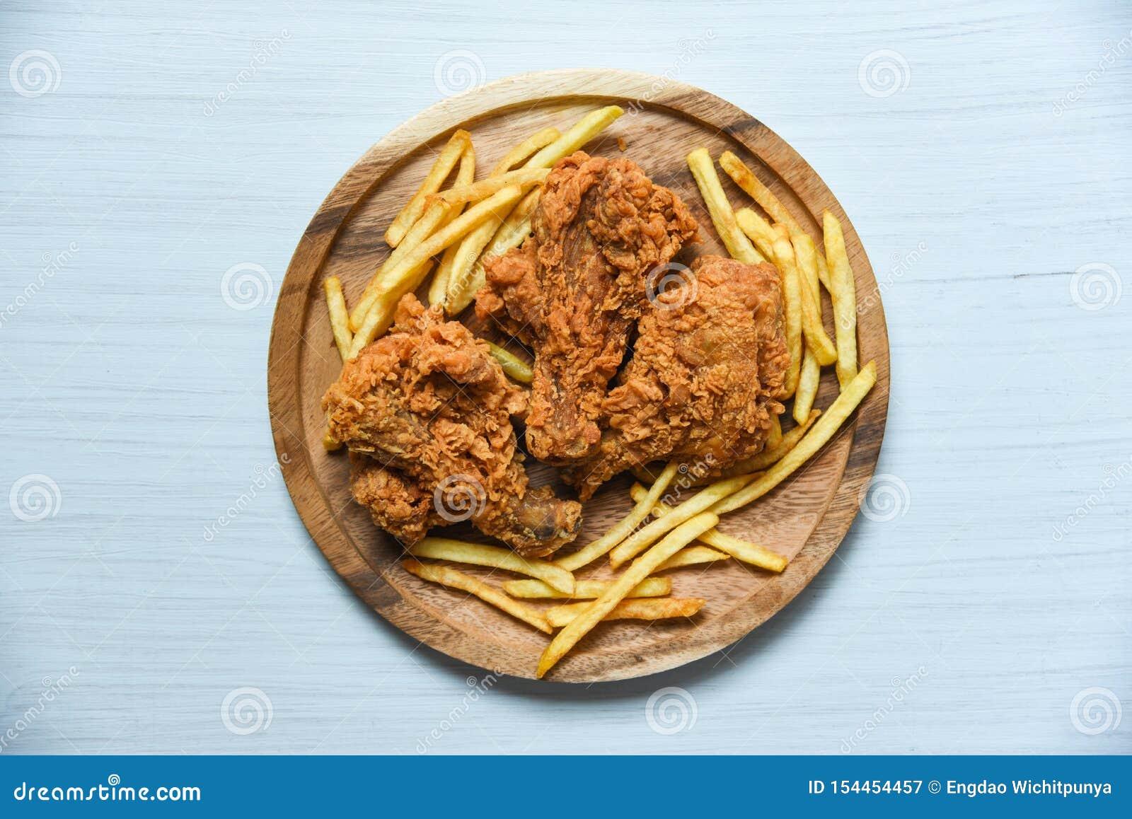 Poulet frit croustillant sur le plateau en bois avec des pommes frites sur le fond de table de salle ? manger