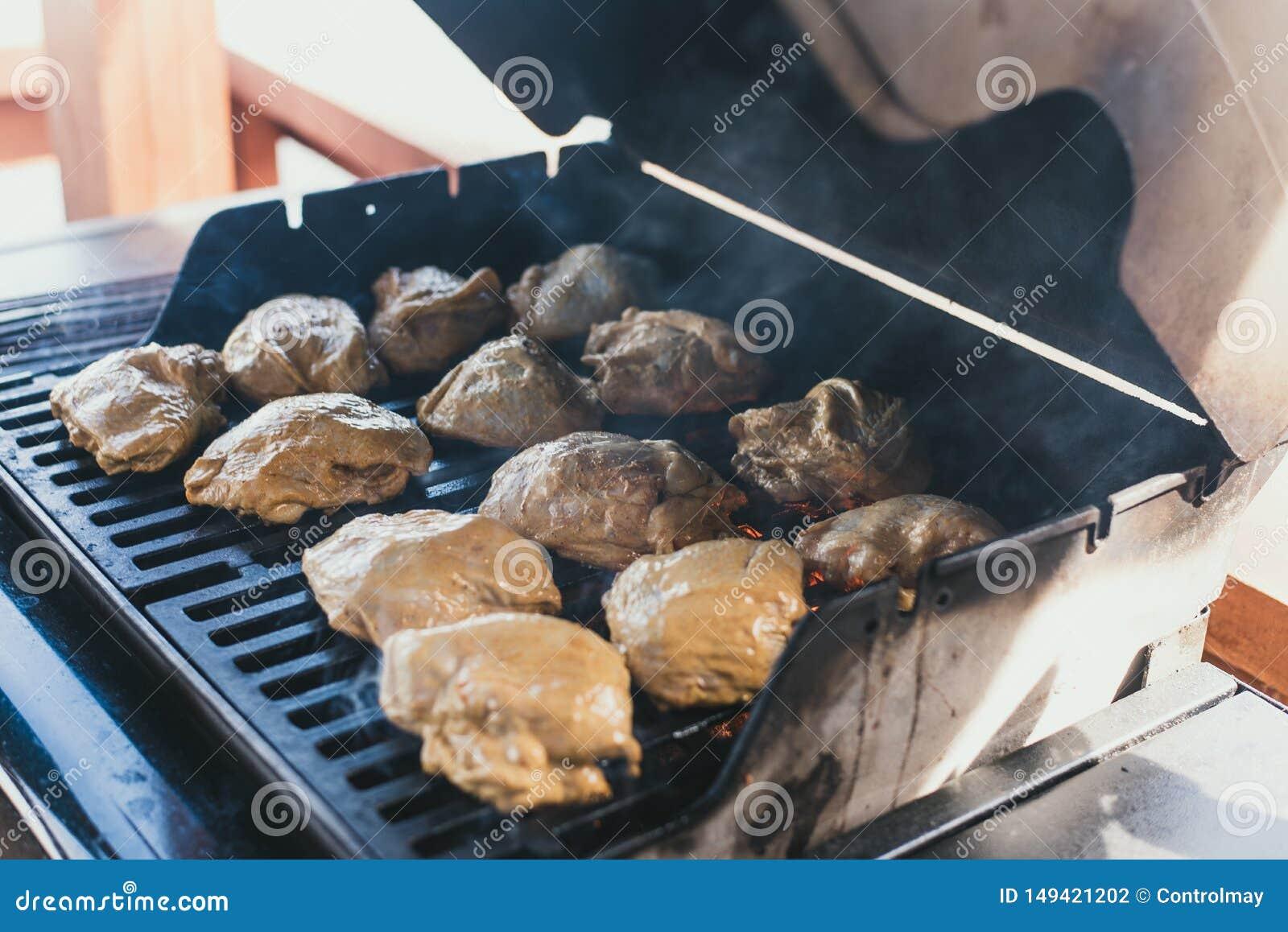 Poulet grillé à un pique-nique L homme a étendu le poulet dans la marinade sur le gril pour sa préparation Grandes carcasses enti