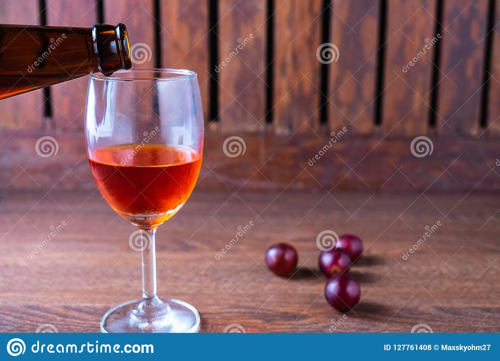 Pour red wine into a glass of wine on a wooden background.