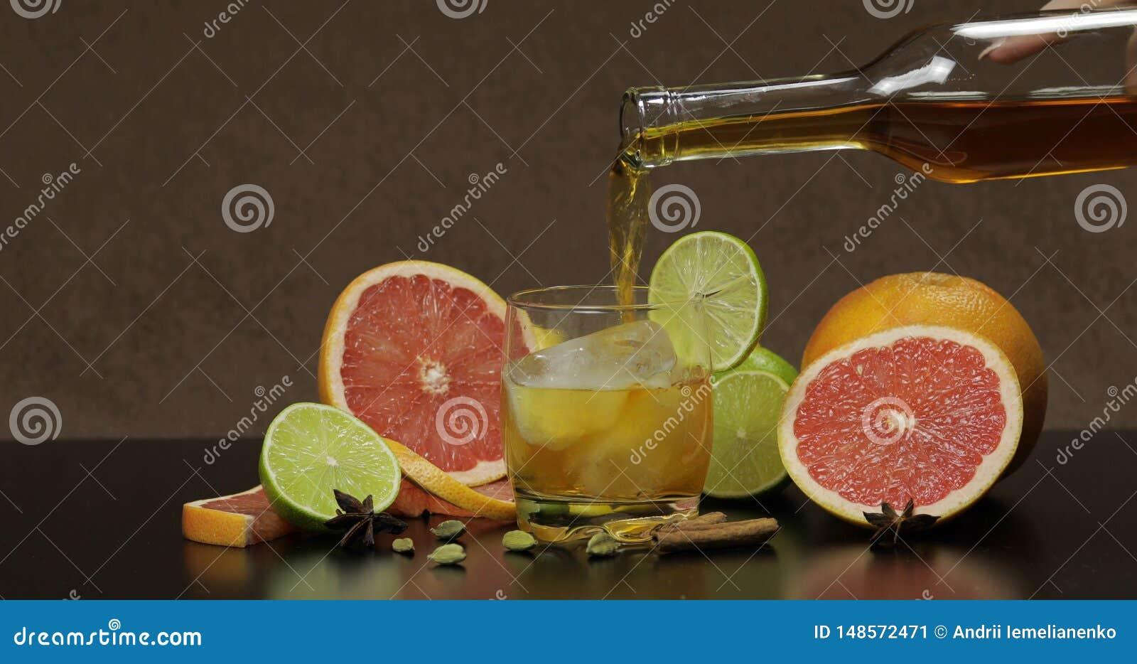 Pour whiskey, cognac, liqueur from a bottle into a glass cup