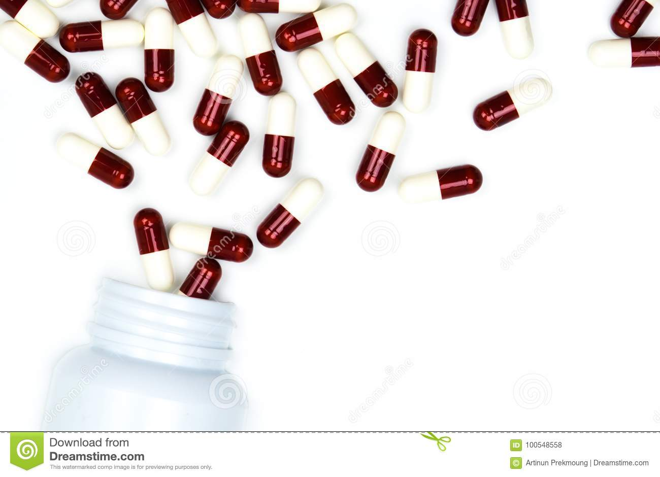 Pouring antibiotics capsule pills into plastic bottle isolated on white background with copy space.